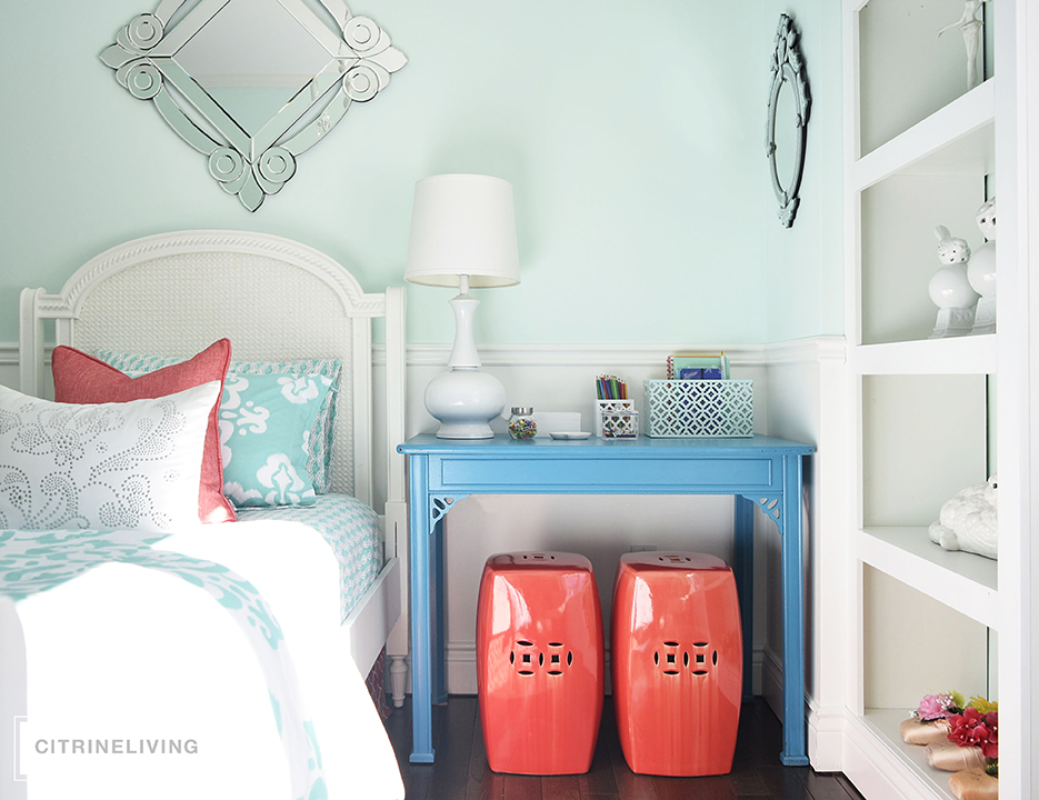 Girl's bedroom featuring turquoise desk as nigh table and coral garden stools.