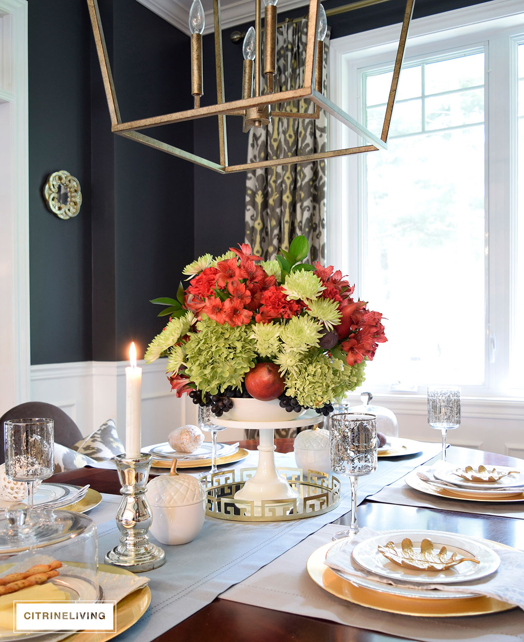 Fall tablescape with metallic touches featuring vibrant red, deep plum and verdant green centrepiece