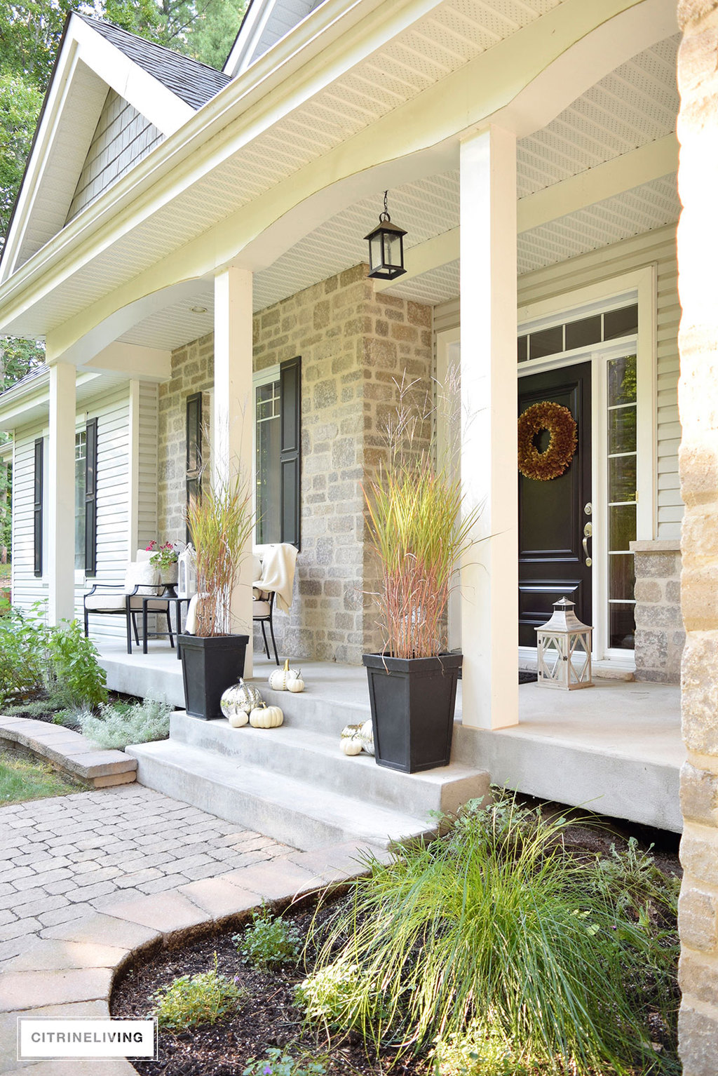Grey and white hime exterior with black details - Fall porch decor featuring mercury glass pumpkins and potted grass