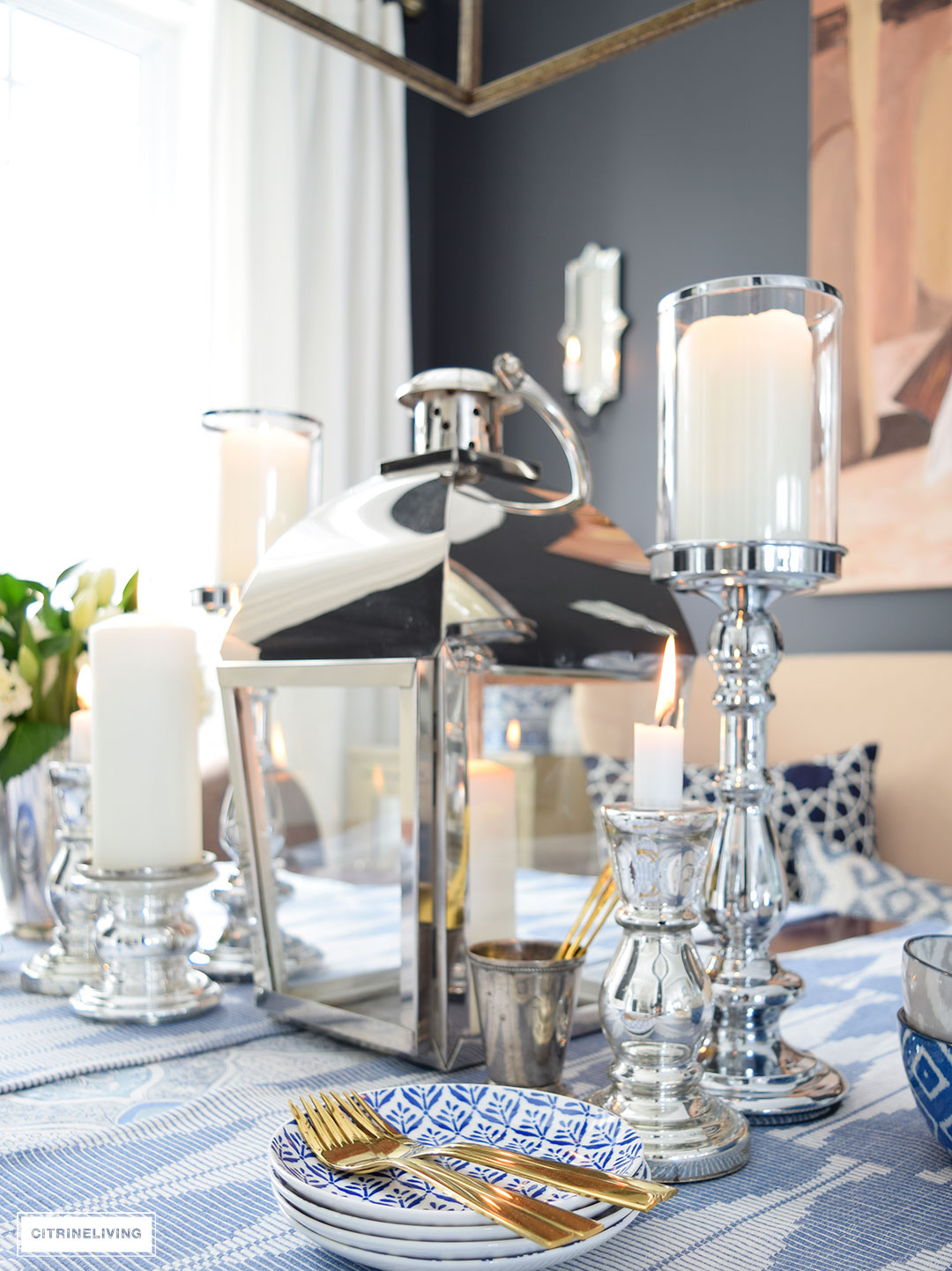 A large silver lantern flanked by silver and mercury glass candleholders make a strong statement as the focal point of your table.