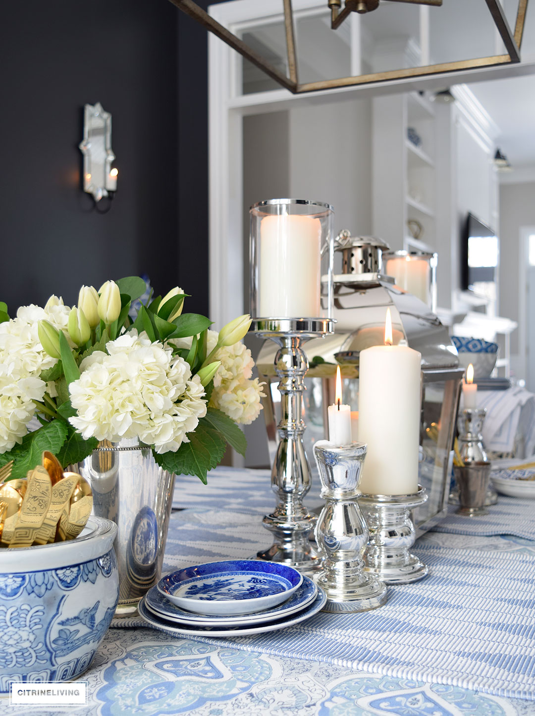 Layers of blue and white pattern with silver candleholders and gold flatware is perfect for a Spring table.