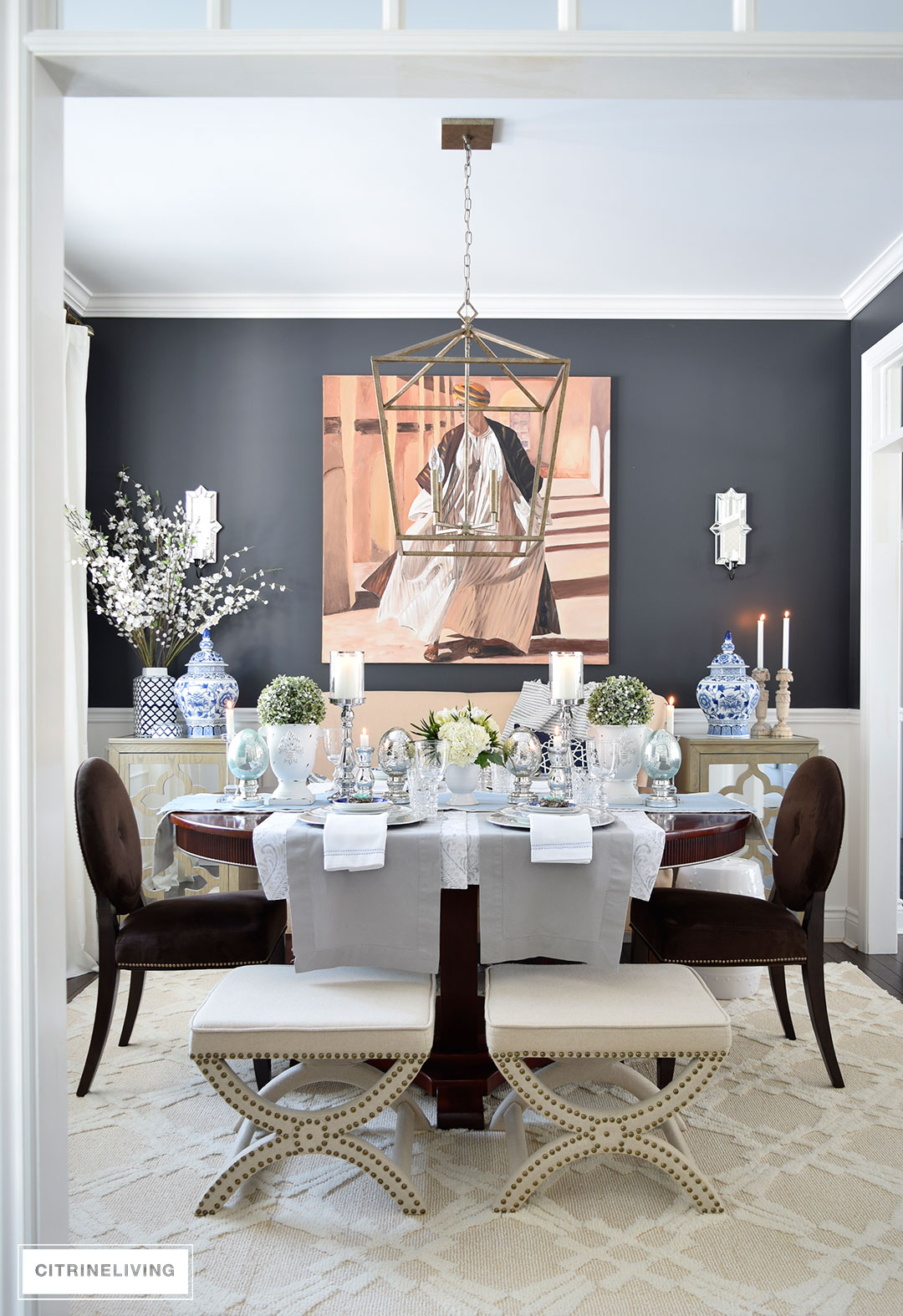 Easter Tablescape set in dining room with elegant black wall color, Cracked Pepper Behr Paint, upholstered stools and settee create an unexpected seating arrangement.