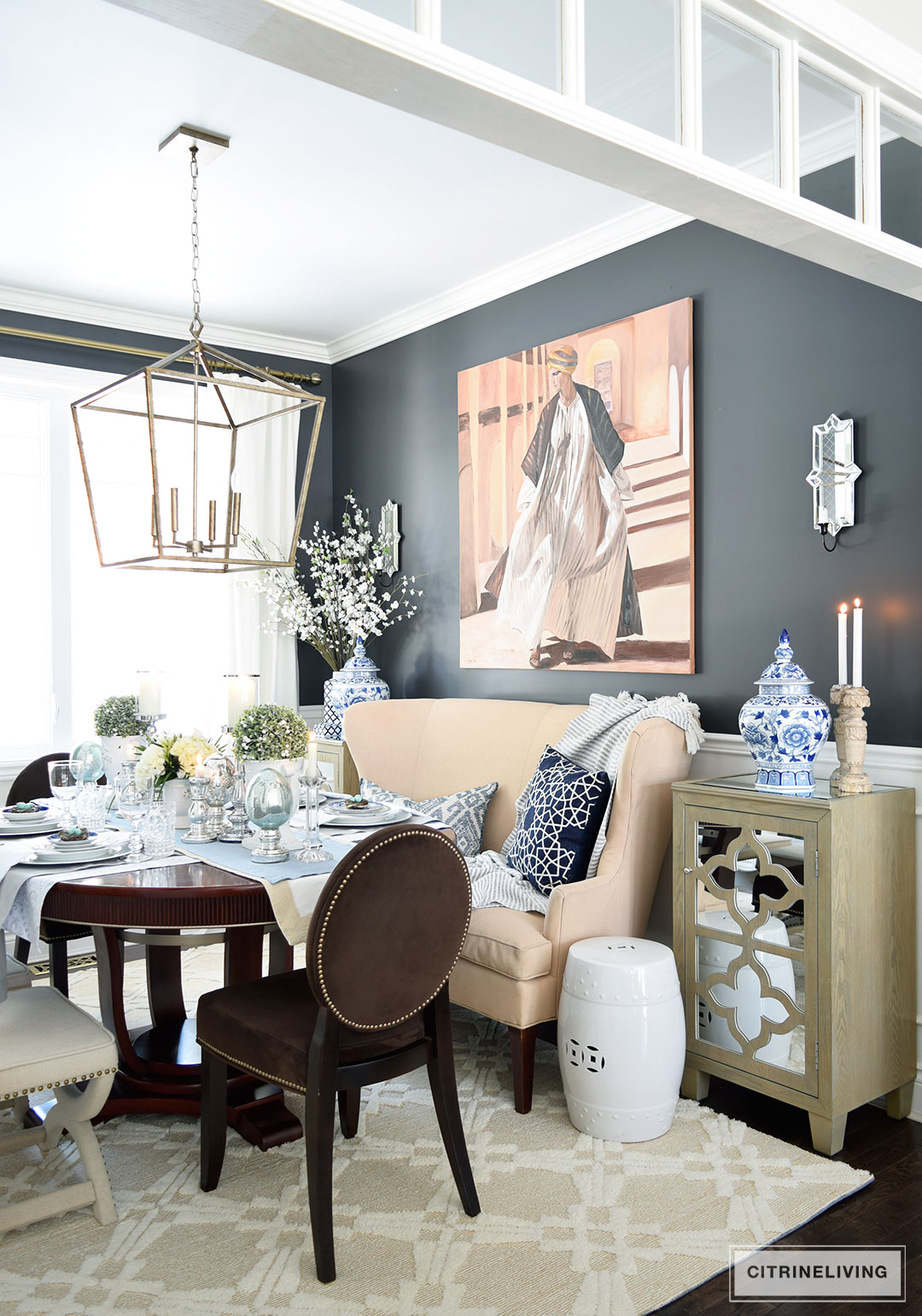 Elegant dining room with black walls and blue and white chinoiserie accents. A simple Easter or Spring tablescape with metallic accents adds sophistication.