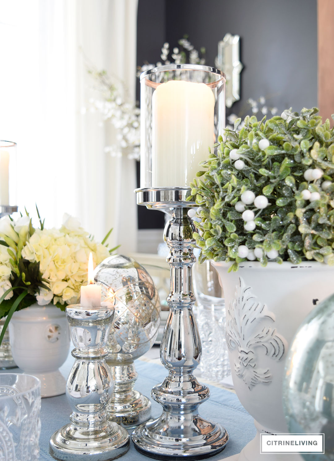 Silver candleholders, mercury glass accessories and topiaries are the perfect mix for and elgegant Easter or Spring tablescape.