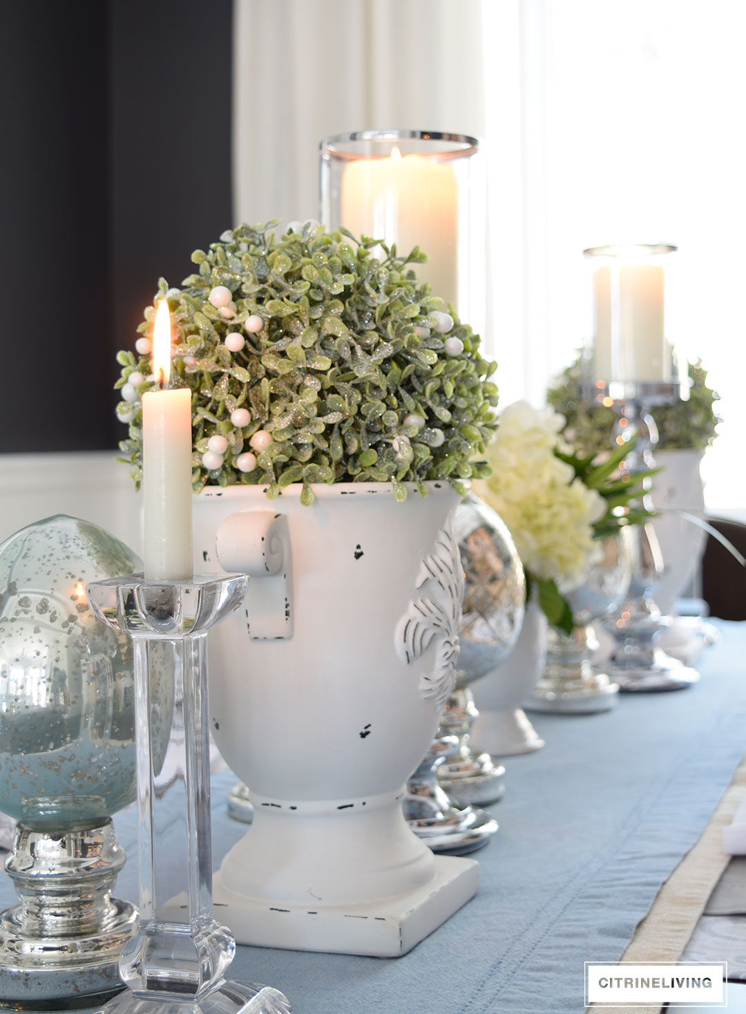 Easter or Spring tablescape with topiaries set in white urns, mixed with mercury glass and crystal accents.