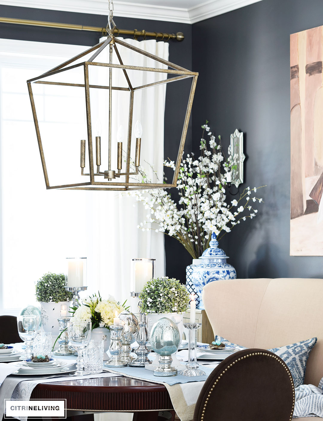 Modern, lantern style pendant chandelier hangs over an elegant Easter tablescape.