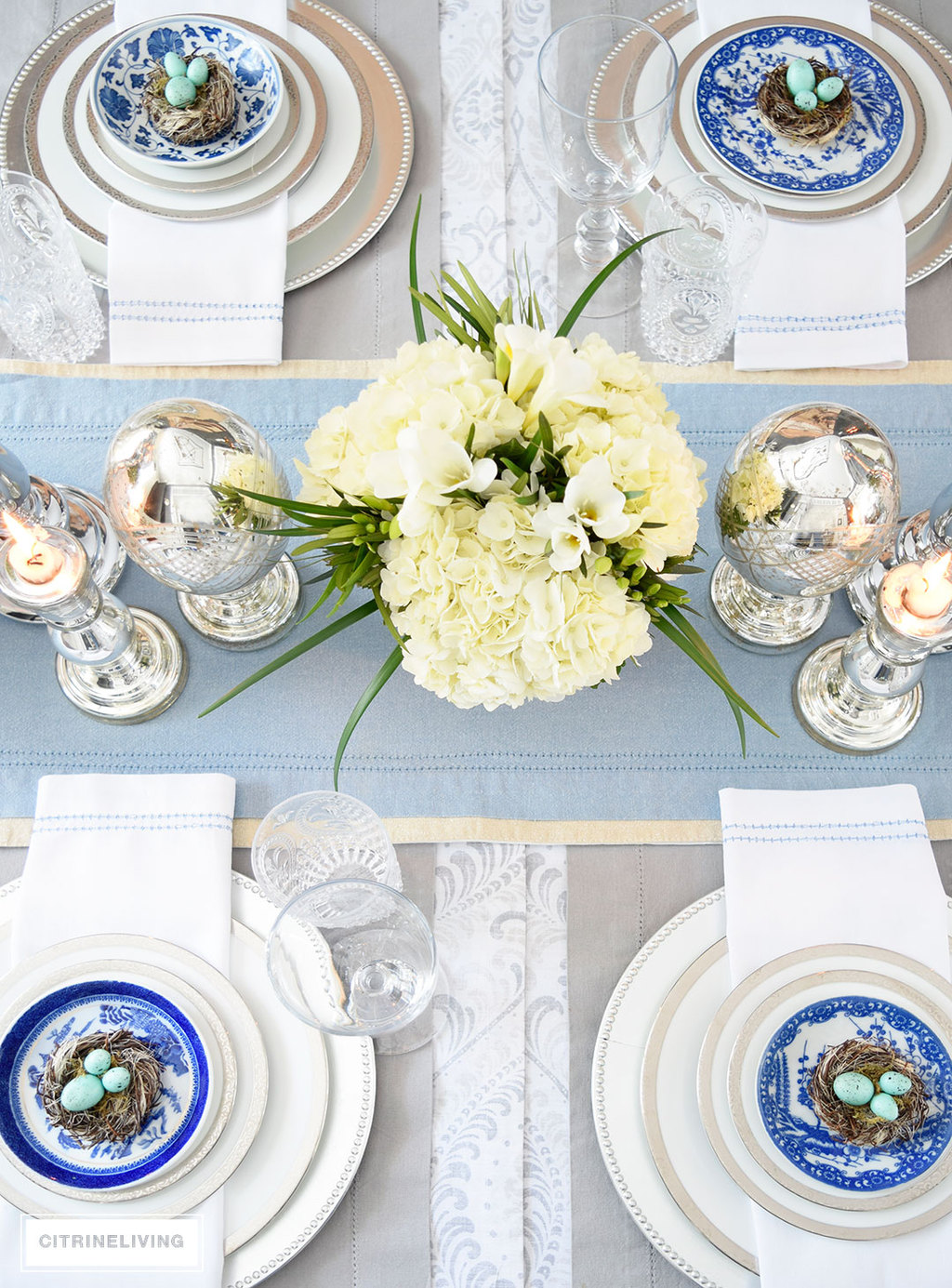A gorgeous Easter tablescape with mercury glass accents and a mix of silver and white with blue and white china. Fresh and beautiful white hydrangeas are the perfect centerpiece.