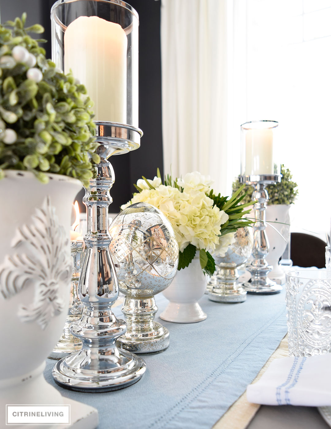 Silver candle holders, mercury glass accessories, topiaries and a white hydrangea arrangement are elegant and sophisticated for Easter and Spring tablescapes.