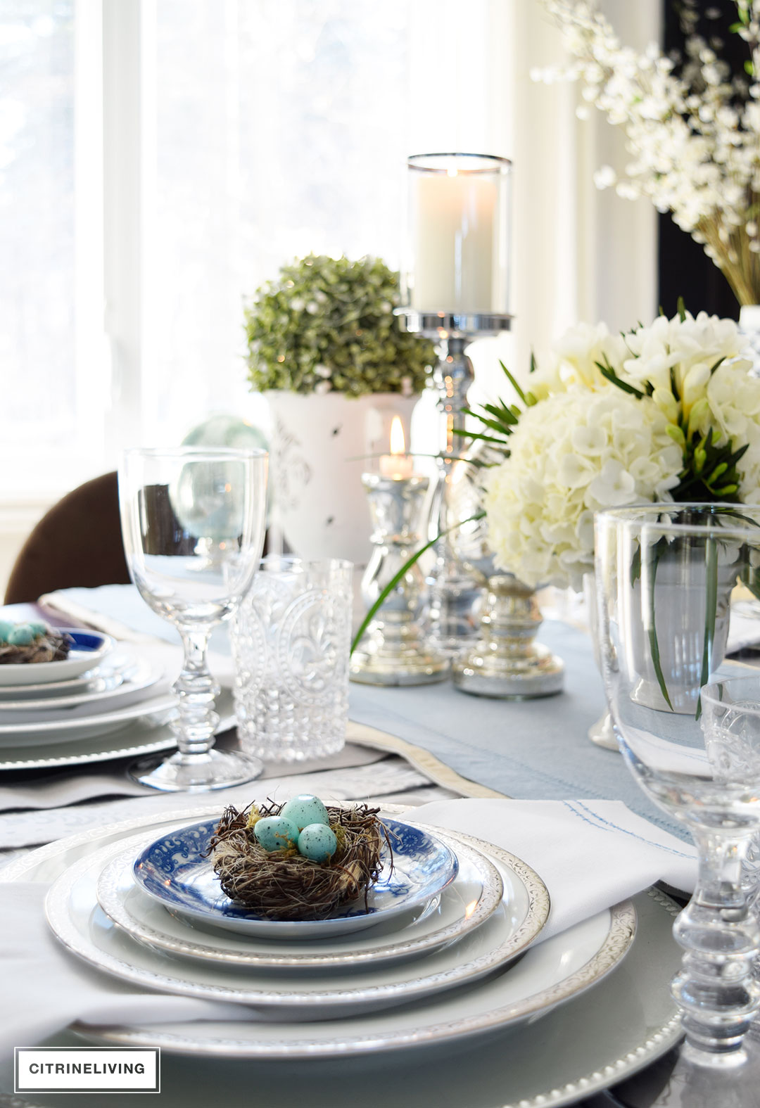 Elegant Easter and Spring tablespcae with mercury glass accents, mixed with fresh and faux florals and greenery. Blue and white china add a classic element.