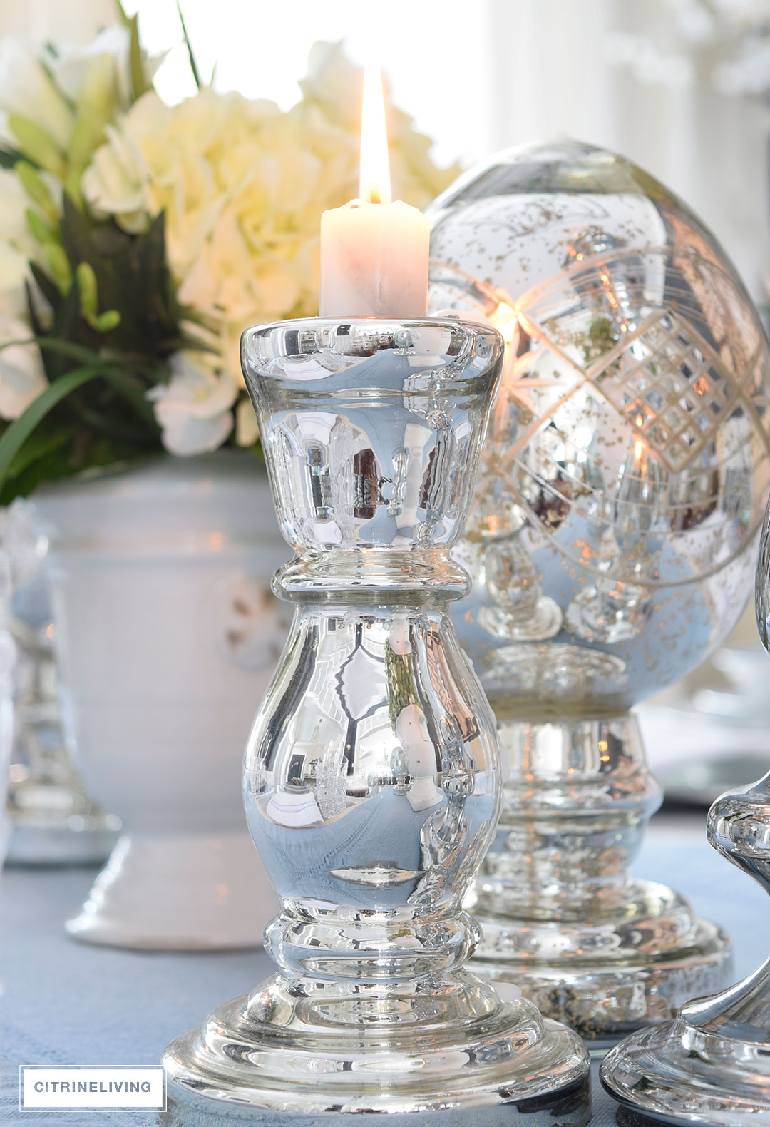 Sparkling mercury glass candleholder and etched Easter egg accessories add elegance and shine to this sophisticated Easter table.