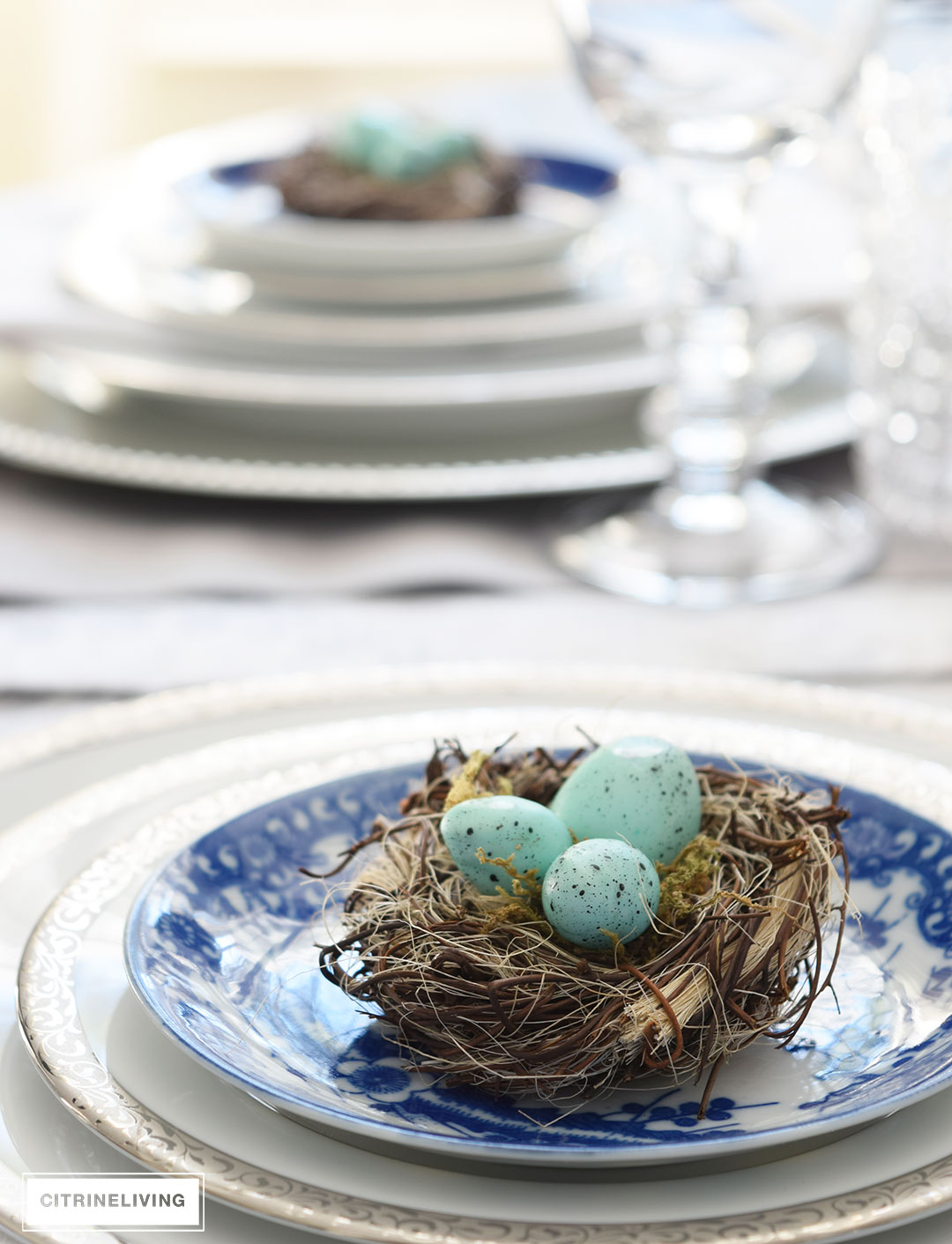 Easter or Spring table setting with pale turquoise eggs atop a mix of blue and white and silver china.