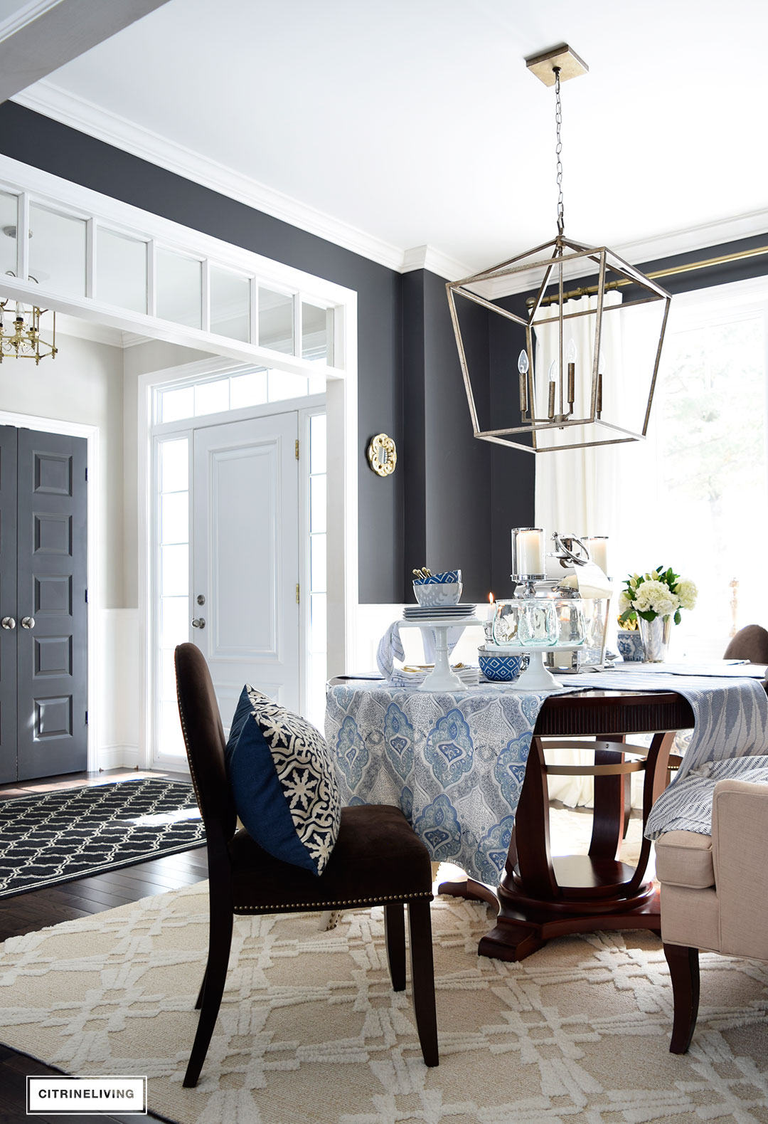 Bright, open concept dining room with a blue and white table set for Spring entertaining.
