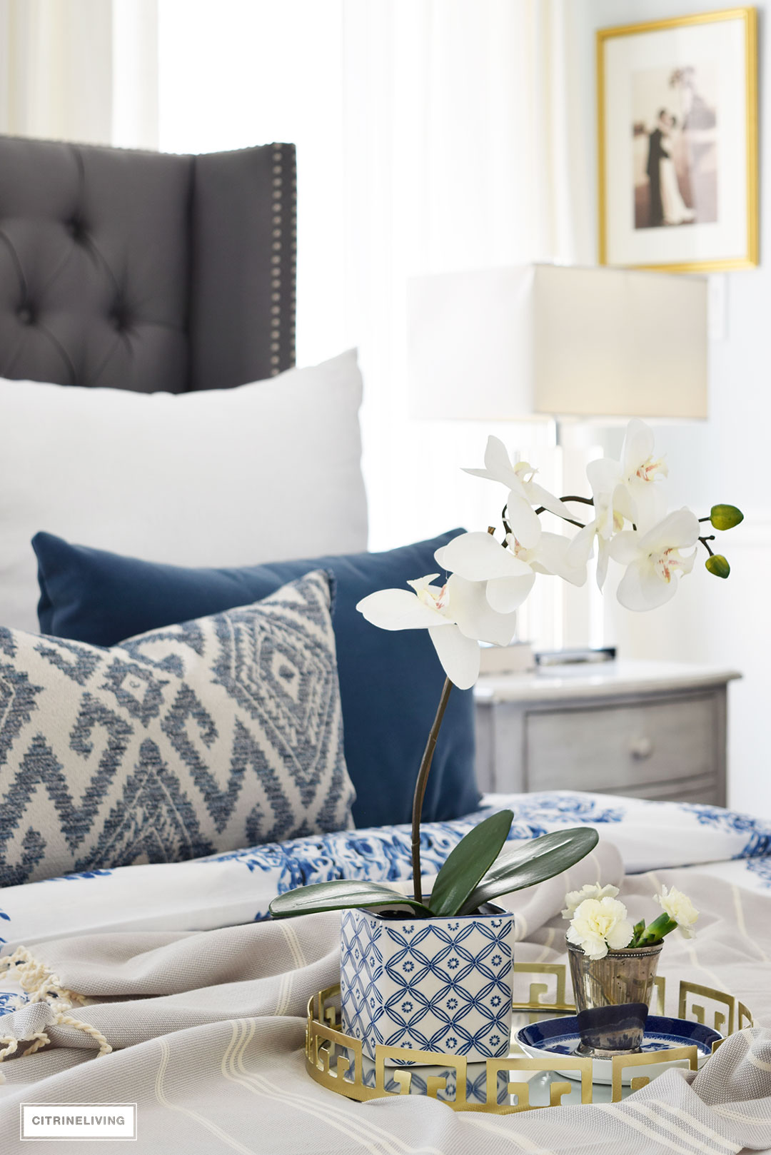 Gorgeous blue and white bedroom featuring blue and white bedding paired with global inspired textiles, grey upholstered bed and brass accents and lighting bring a bright and airy look to any bedroom. Layer your bed with small luxuries to create a true retreat - a gold mirrored tray and florals!