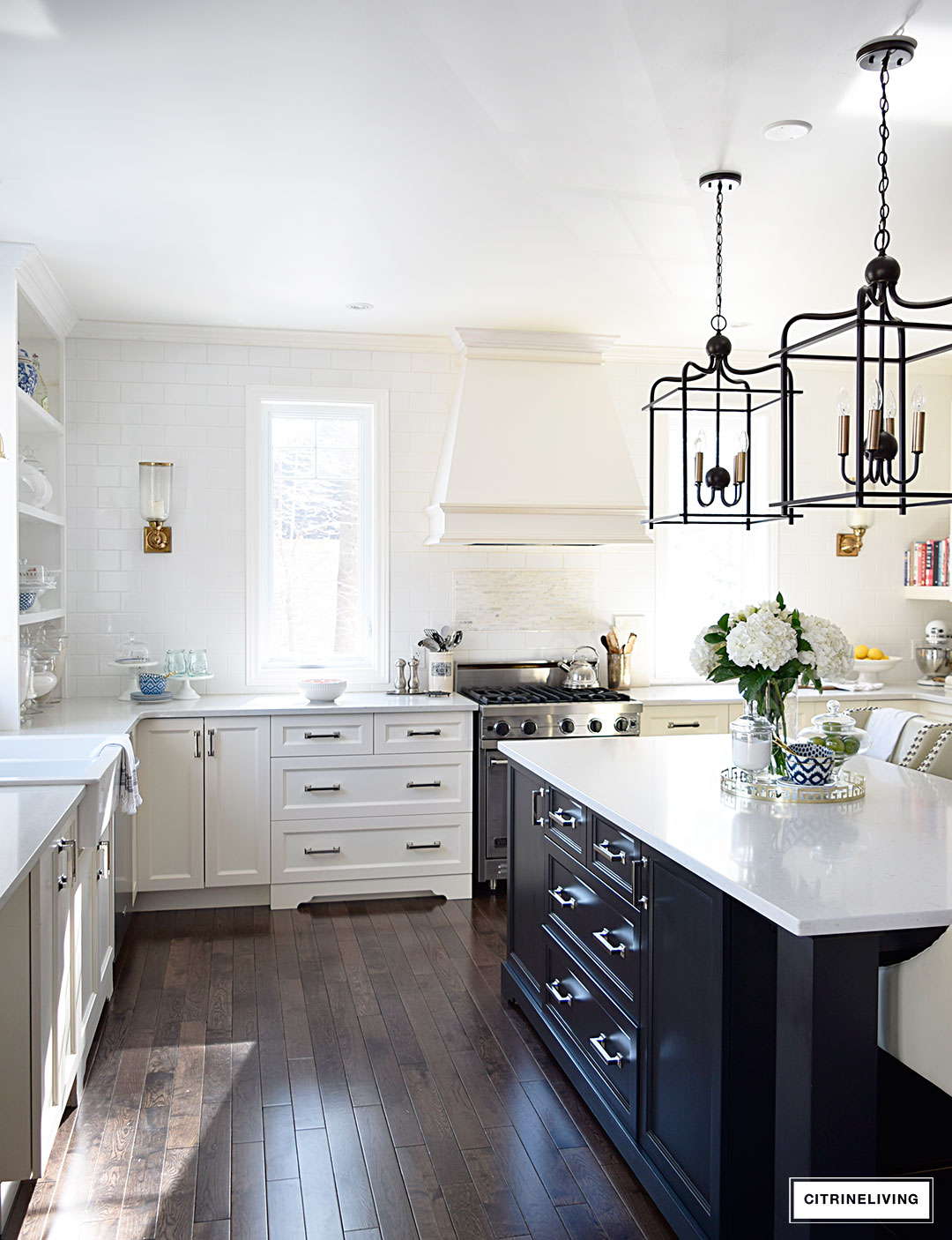 An open concept kitchen with counter to ceiling subway tile, no upper cabinets and mixed metals creates a unique and personal look.