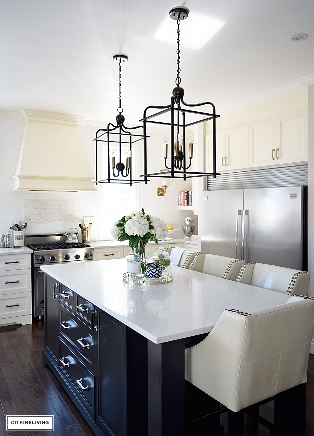 Bright and airy kitchen with lantern style pendant lighting over the island.