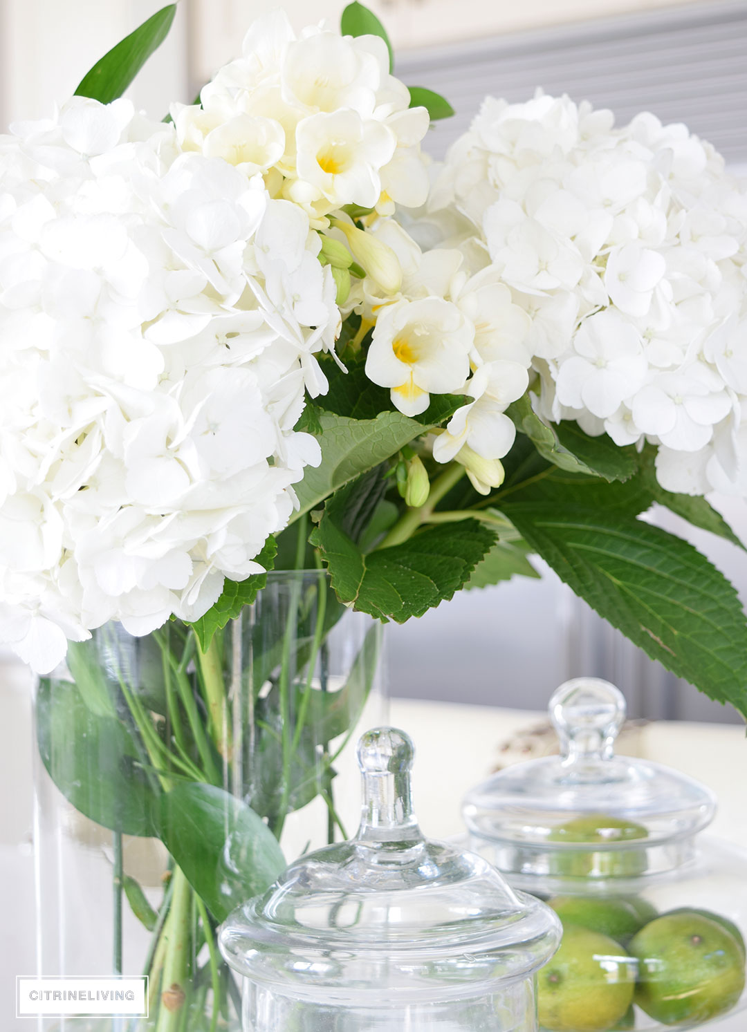 Beautiful hydrangeas and freesias create a beautiful kitchen table centerpiece for Spring and Summer.