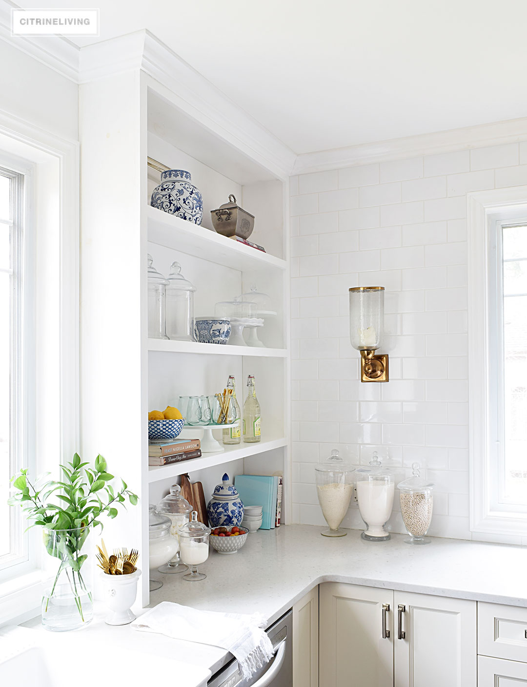 Create a curated, collected, artisanal look on your kitchen shelves with a mix of cookbooks, wood, glass, blue and white, and gourmet inspired accents.