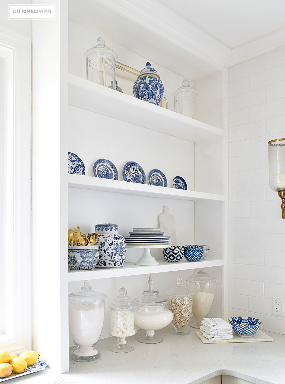 A white kitchen with open shelving is the perfect home for gorgeous blue and white accessories and dishes on display.