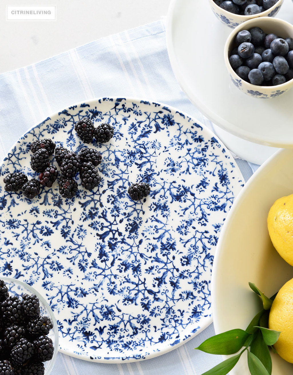 Create a welcoming tablescape of blue and white accented with fresh lemons.