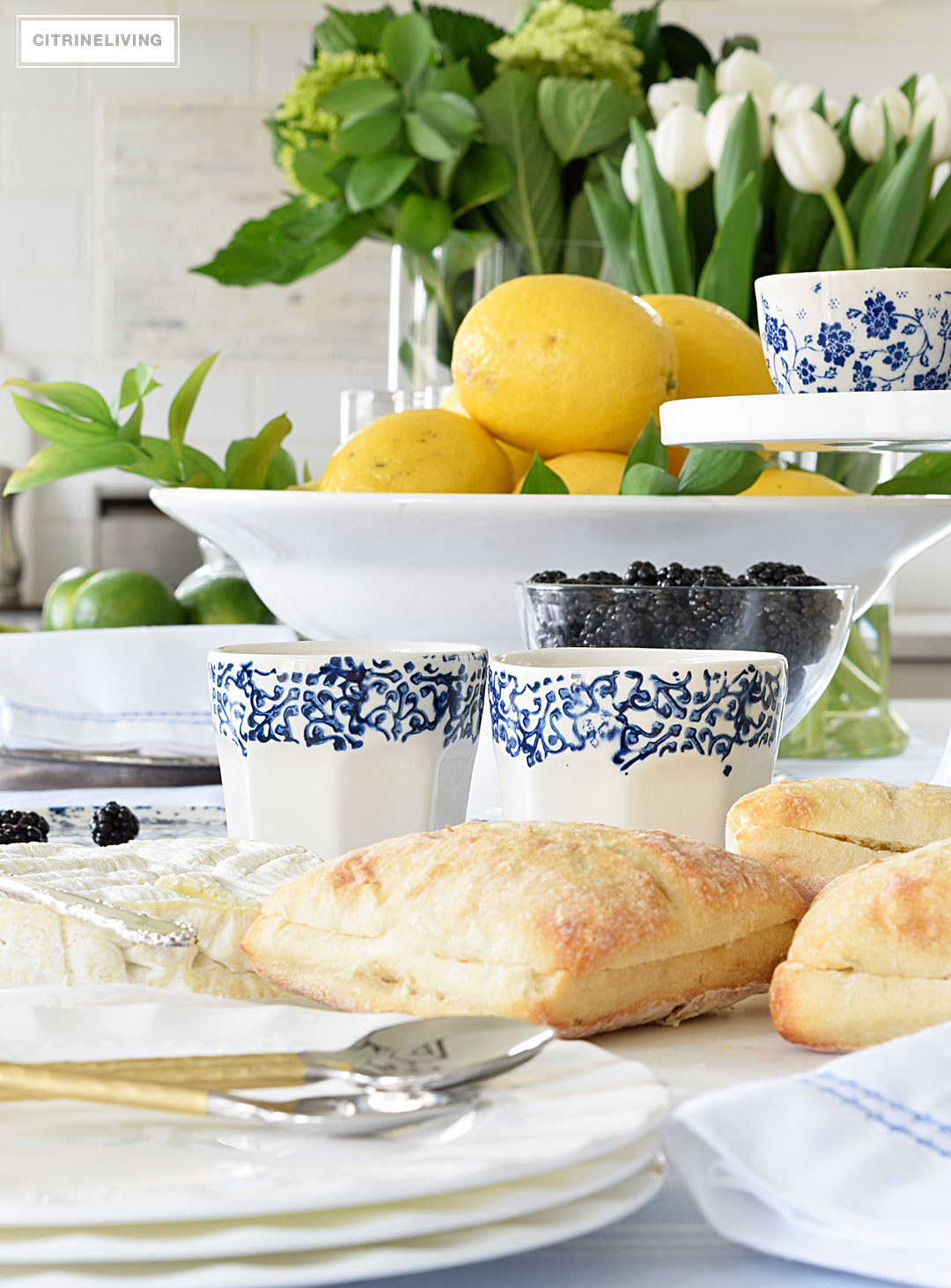 Create a welcoming tablescape of blue and white accented with fresh flowers, lemons and limes.
