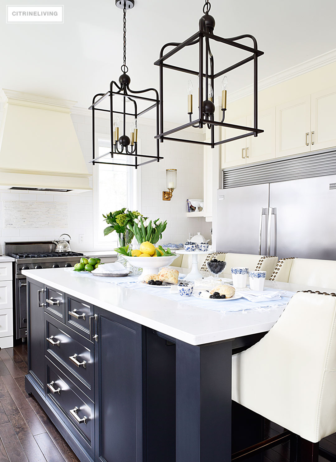 A white kitchen with a welcoming tablescape of blue and white accented with fresh flowers, lemons and limes.