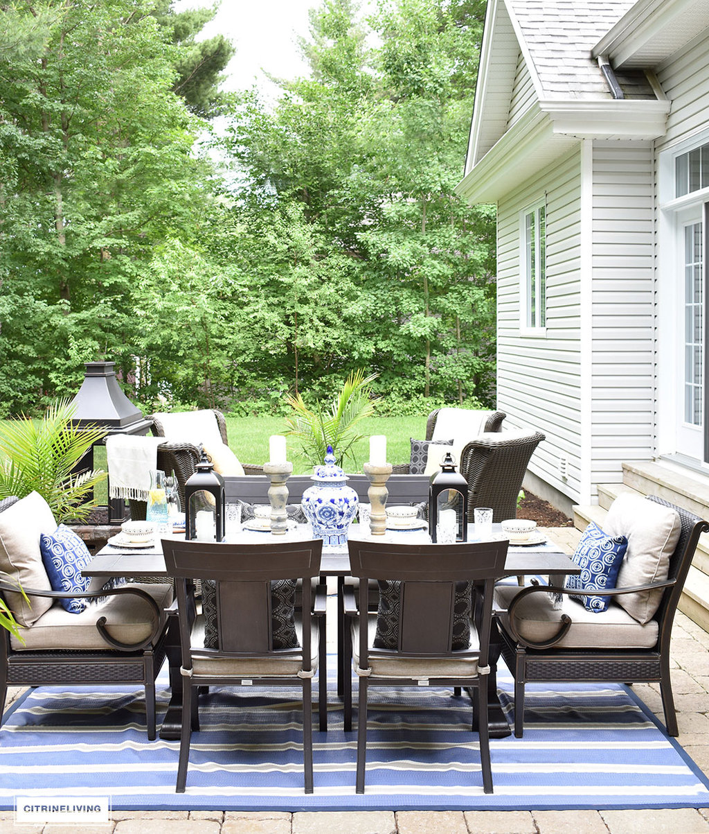 Backyard patio with dining and conversation areas - blue and white striped outdoor rugs and accents bring an indoor look outdoors.
