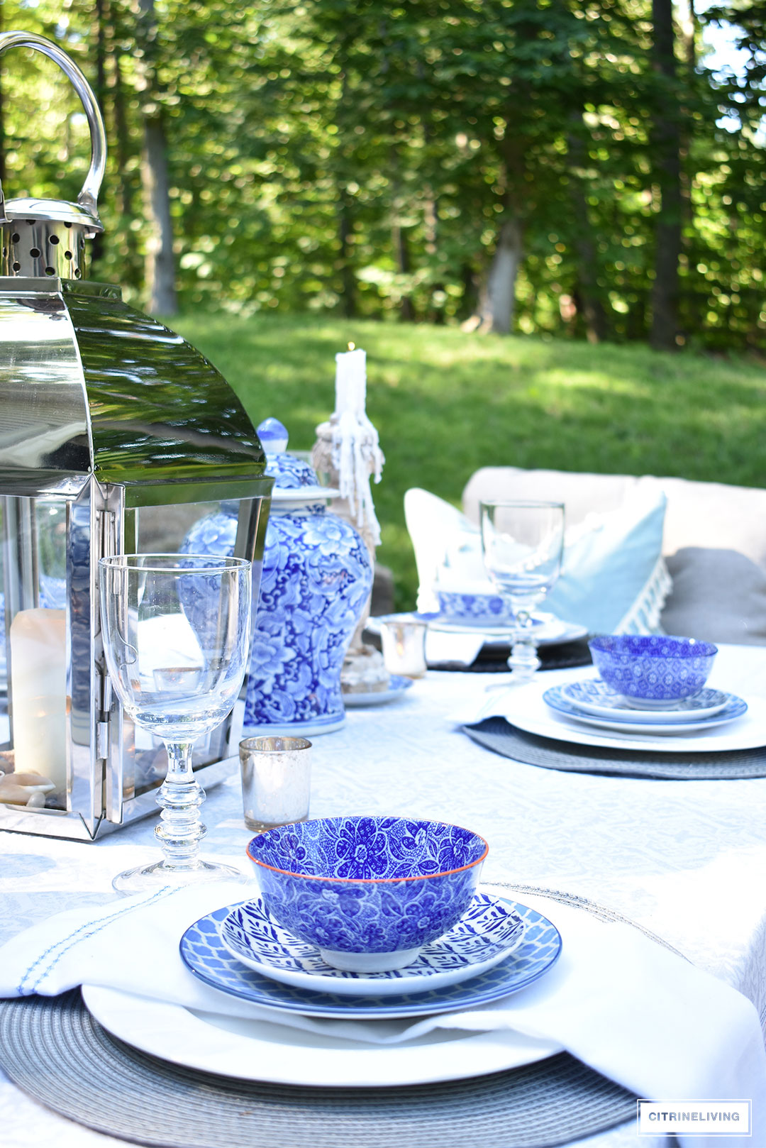 An outdoor tablescape with blue and white ginger jars and a mix of blue and white patterned dishes brings a casual yet elegant look to your outdoor space.