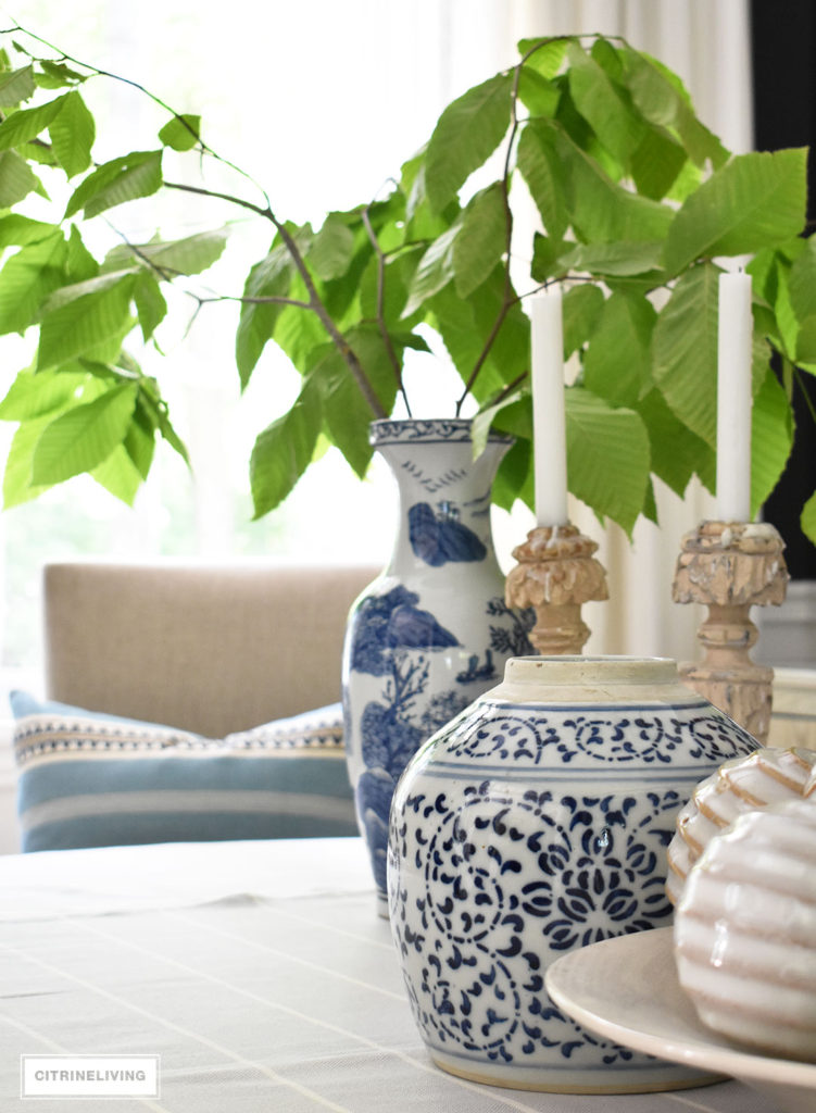Blue and white vases and ginger layered with textured neutrals create a soothing and classic look, Fresh cut greenery is a simple and elegant touch of Summer decor.