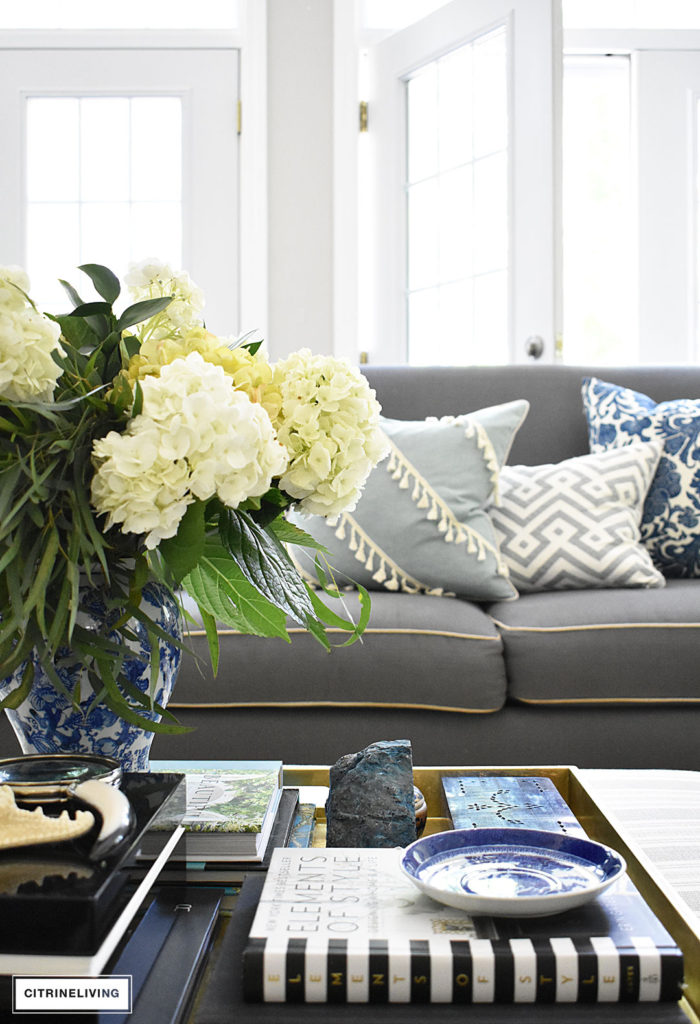 Summer decorated living with layers of beautiful blue patterned pillows, accented with fresh hydrangeas and greenery arranged in a blue an white ginger jar. Blue accessories and coastal elements enhance the Summer theme.