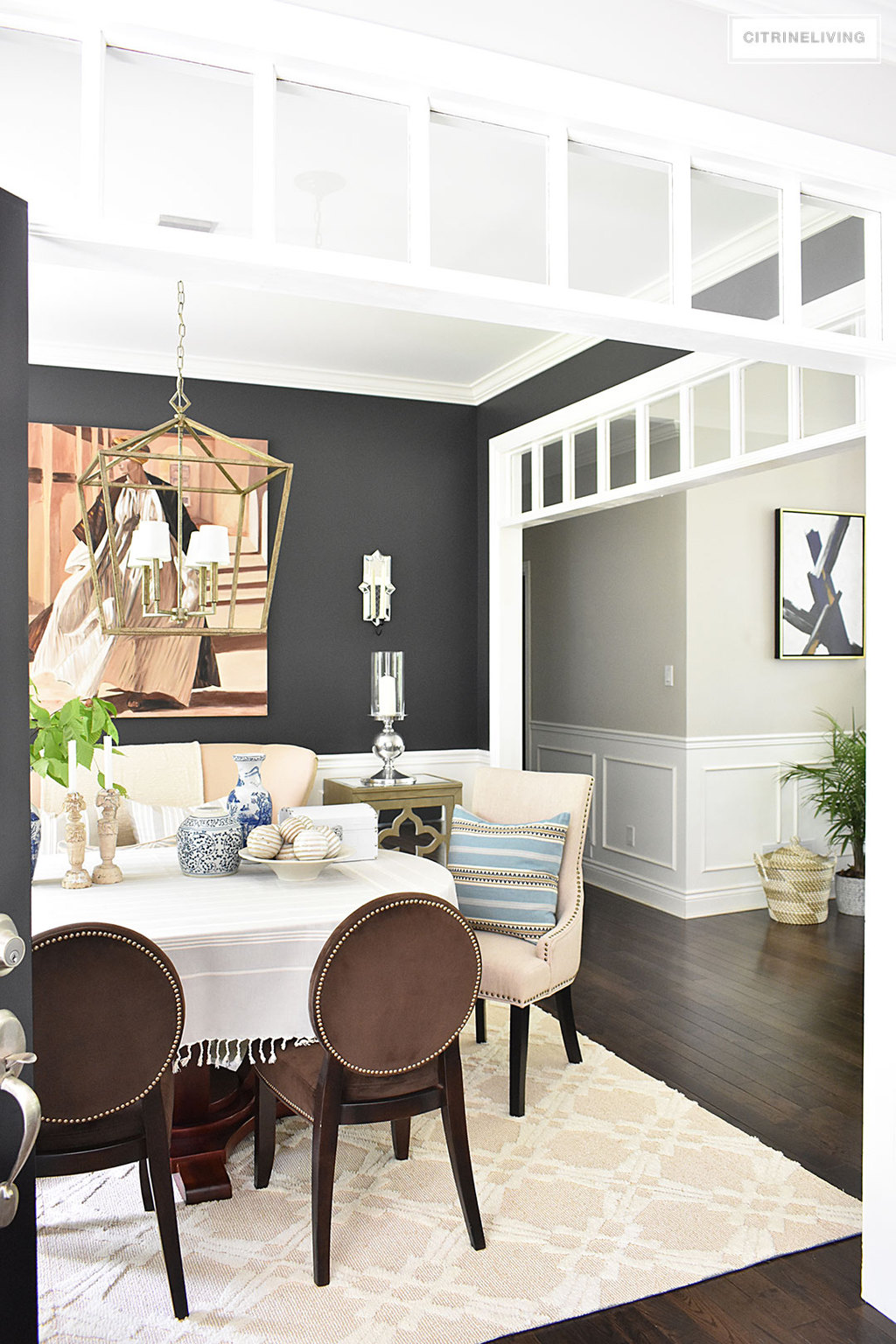 Sophisticated and elegant dining room with transom details. Black walls painted in Cracked pepper by Behr Paint. Neutral decor with layers of blue and white pottery. Upholstered chairs with antique brass nailed trim are elegant and refined. Large scale lantern pendant chandelier makes a bold statement.