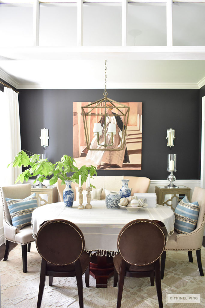 Sophisticated and elegant dining room with transom details. Black walls painted in Cracked pepper by Behr Paint. Neutral decor with layers of blue and white pottery. Upholstered chairs with antique brass nailed trim are elegant and refined. Large scale lantern pendant chandelier makes a bold statement. Tailored, custom white and grey pinstripe drapes and layers of striped textiles are classic touches.