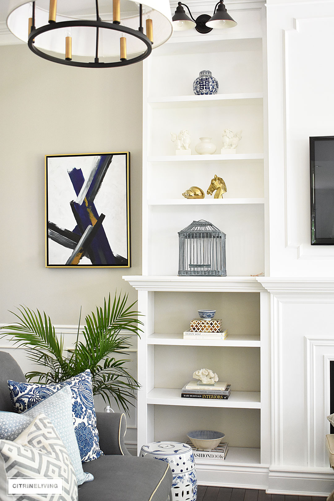 Summer decorated living with layers of beautiful blue patterned pillows accented with fresh palms. Custom built bookshelves hold blue and white pieces mixed wit coastal accessories, brass accents and design books.