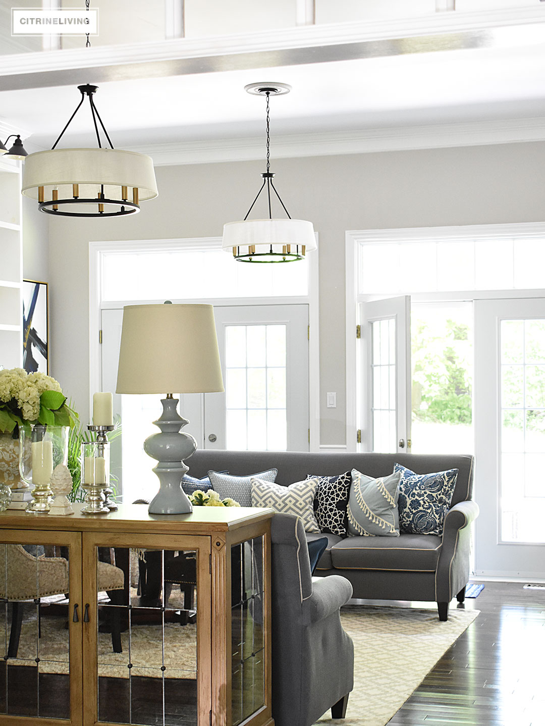 Elegant, open concept living room, with with grey sofas and drum shade pendant lights create a neutral backdrop of layers of beautiful blue patterned pillows. Decorated for Summer with fresh cut greenery, hydrangeas and palms.