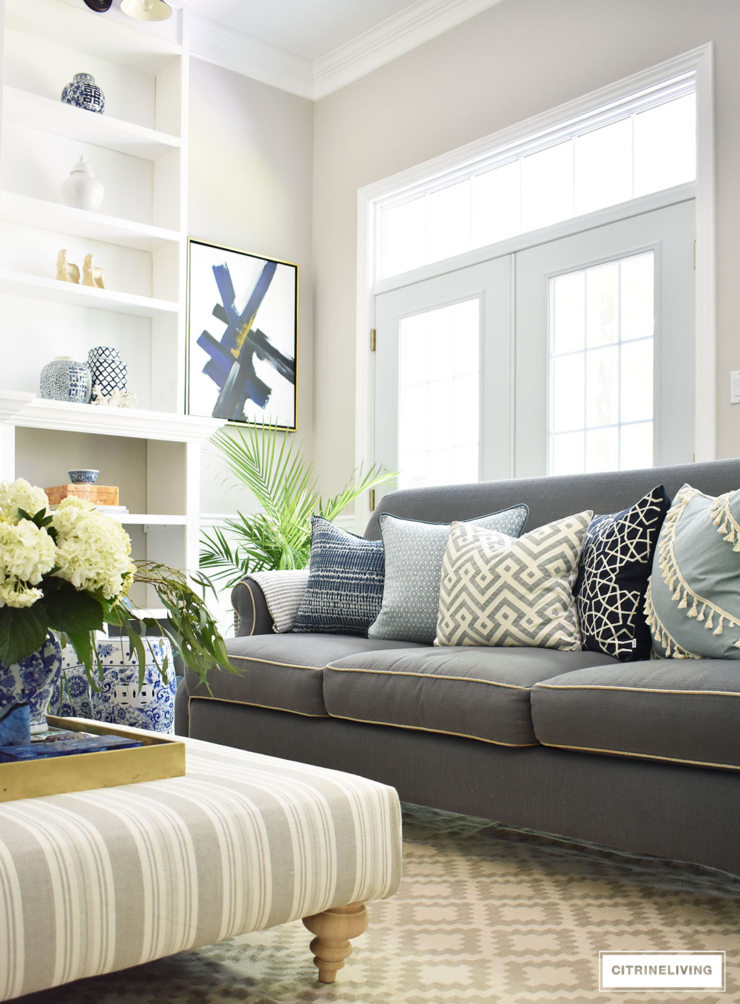 Summer decorated living with layers of beautiful blue patterned pillows accented with fresh palms. Custom built bookshelves hold blue and white pieces mixed wit coastal accessories, brass accents and design books. A striped upholstered ottoman makes a classic statement.