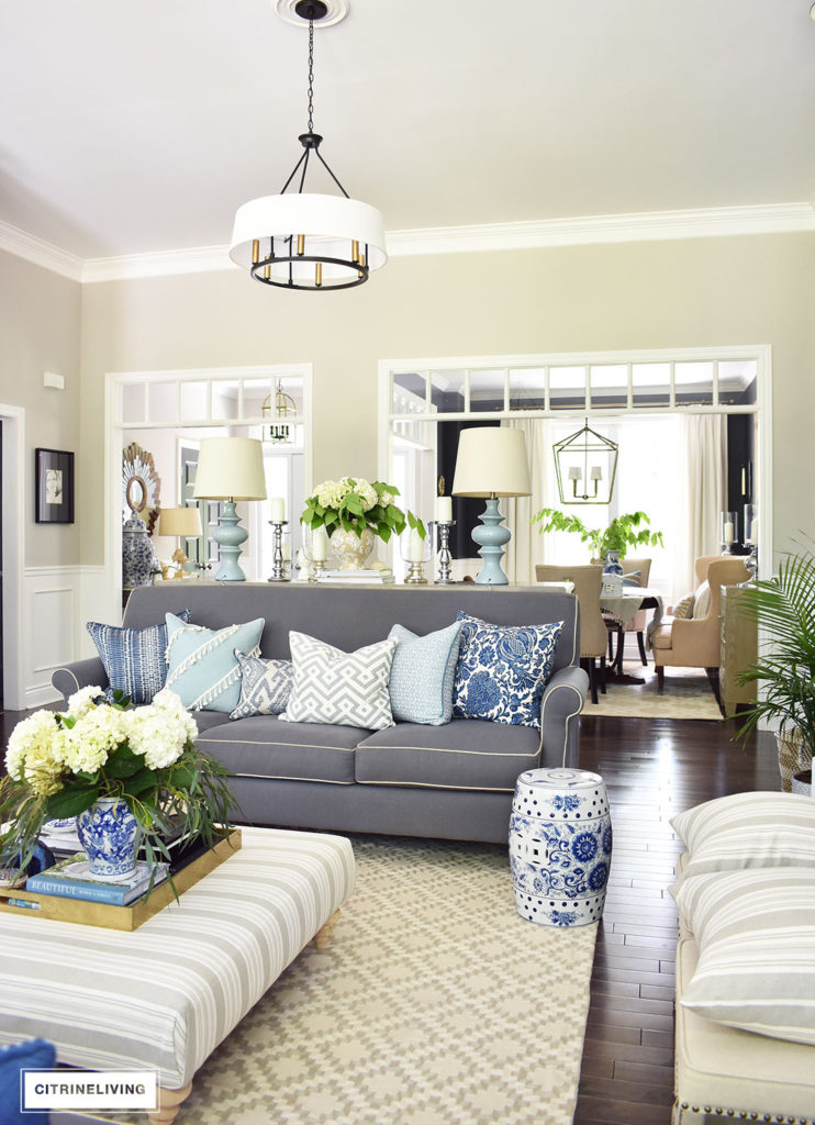 Elegant, open concept living room, with with grey sofas and drum shade pendant lights create a neutral backdrop of layers of beautiful blue patterned pillows and blue and white pottery and garden stools. Decorated for Summer with fresh cut greenery, hydrangeas and palms.
