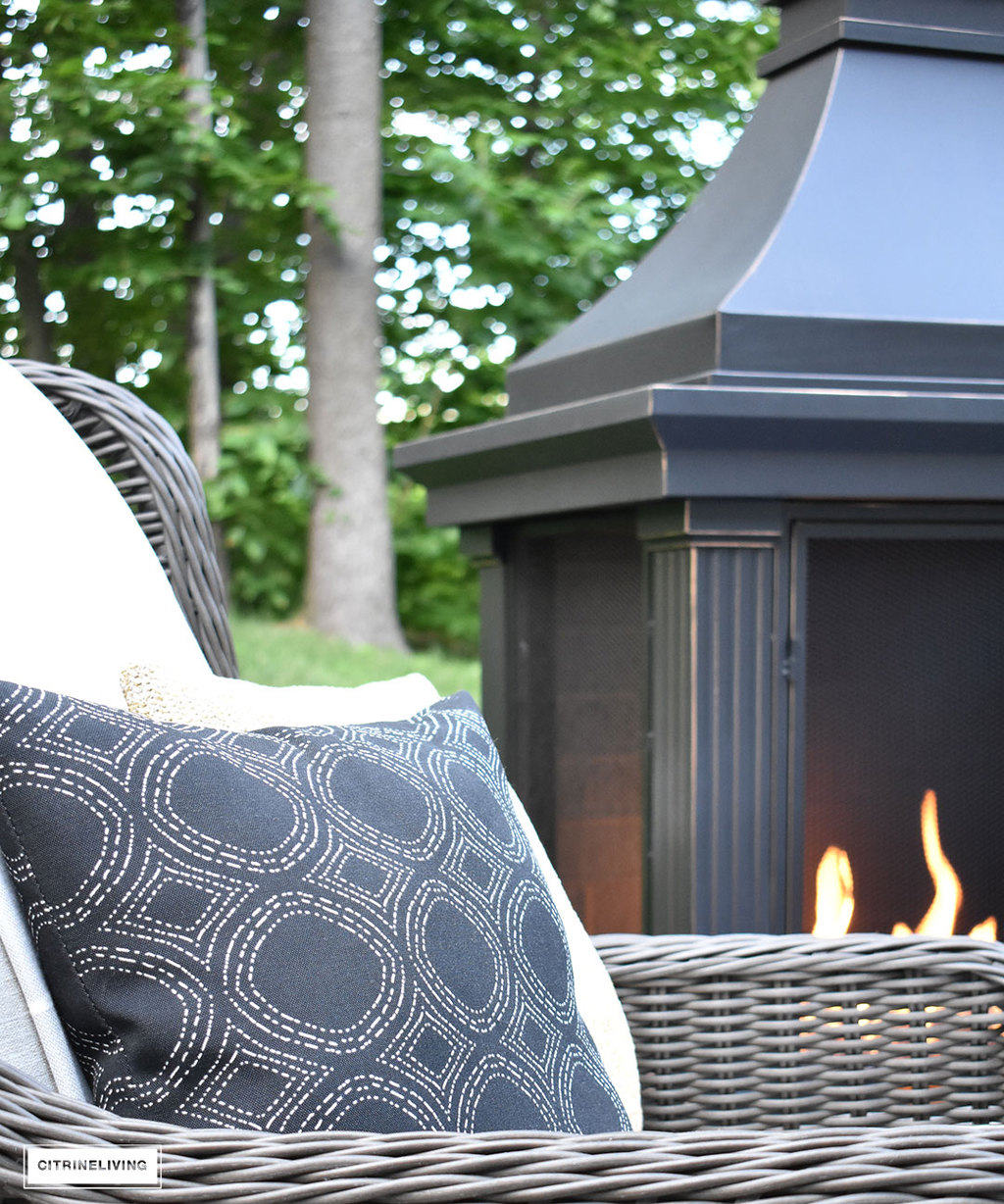 Comfy furniture and layers with pillows and blankets bring the indoors outside by this outdoor fireplace.