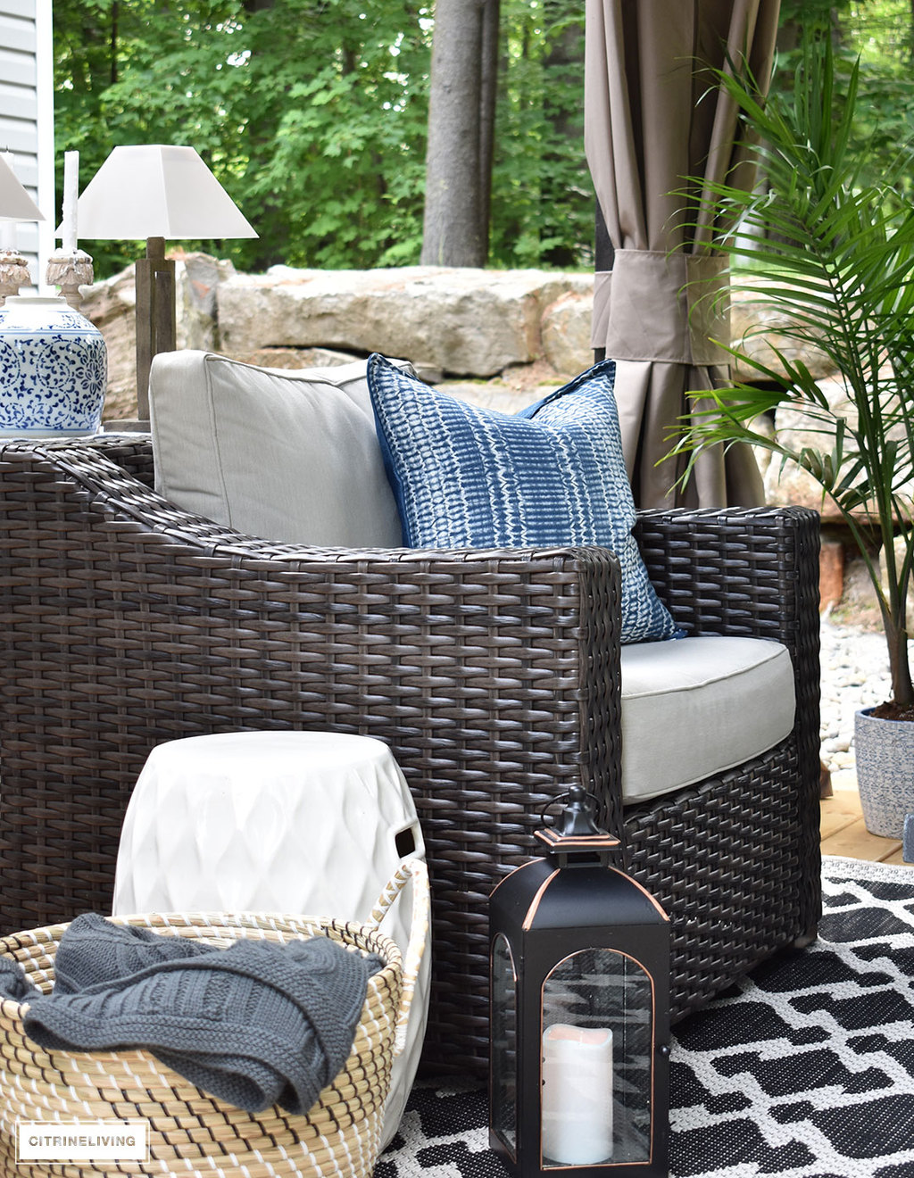 Create a comfortable and inviting outdoor setting with resin wicker club chairs and layered accessories. Blue and white touches are always classic and elegant for Summer decorating outdoors!
