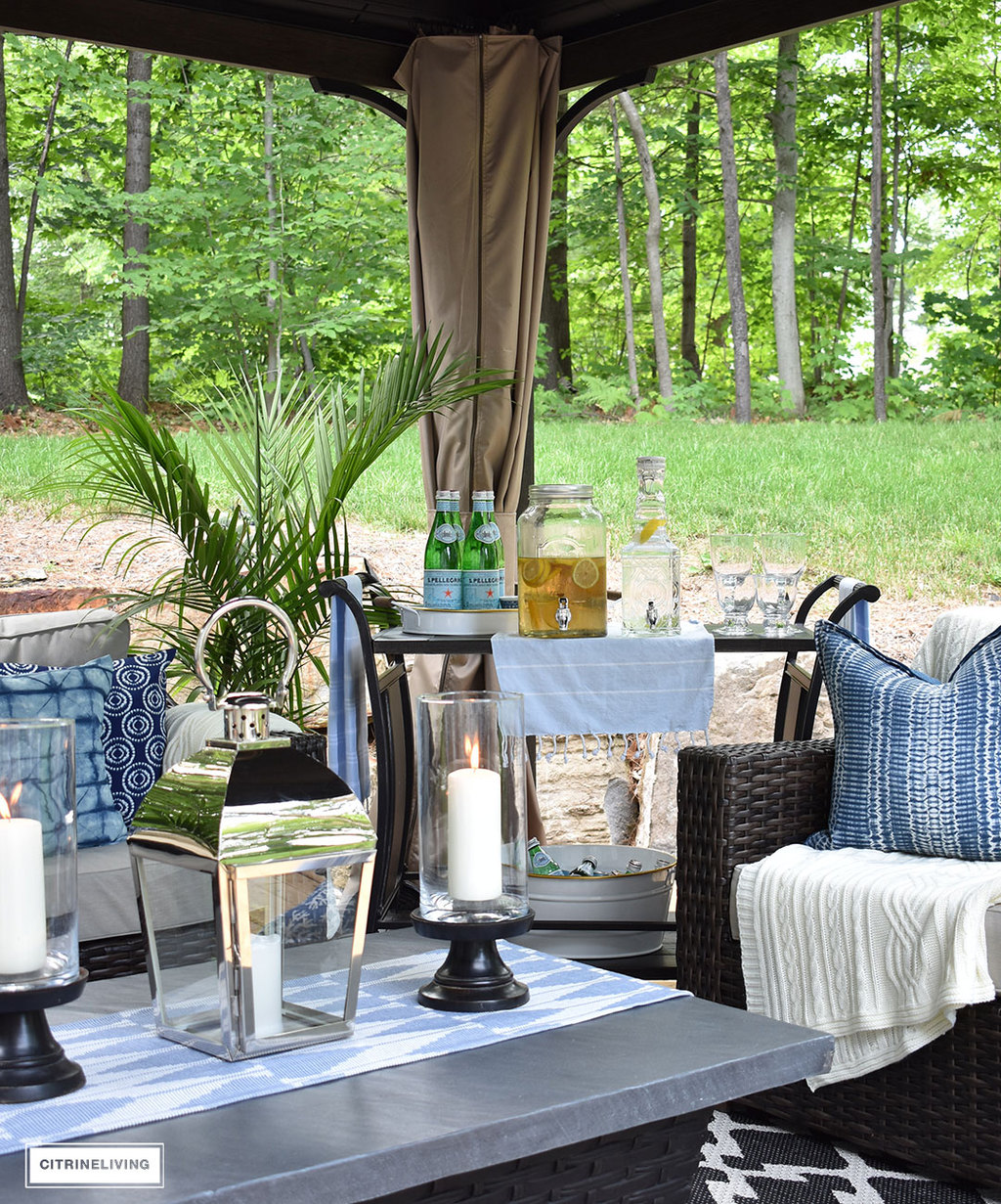 Create the perfect lounging area in your backyard with a beautiful covered gazebo, with added height for an airy, open feel. A gorgeous fire table, solar chandelier, resin wicker furniture, bar cart and layered accessories create an elegant and sophisticated look.