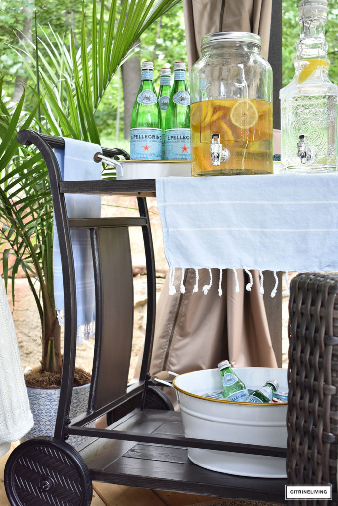 A chic bar cart, fully stocked for guests is the essential accessory for outdoor entertaining! Create an elegant and chic display with trays, and vintage inspired beverage dispensers.