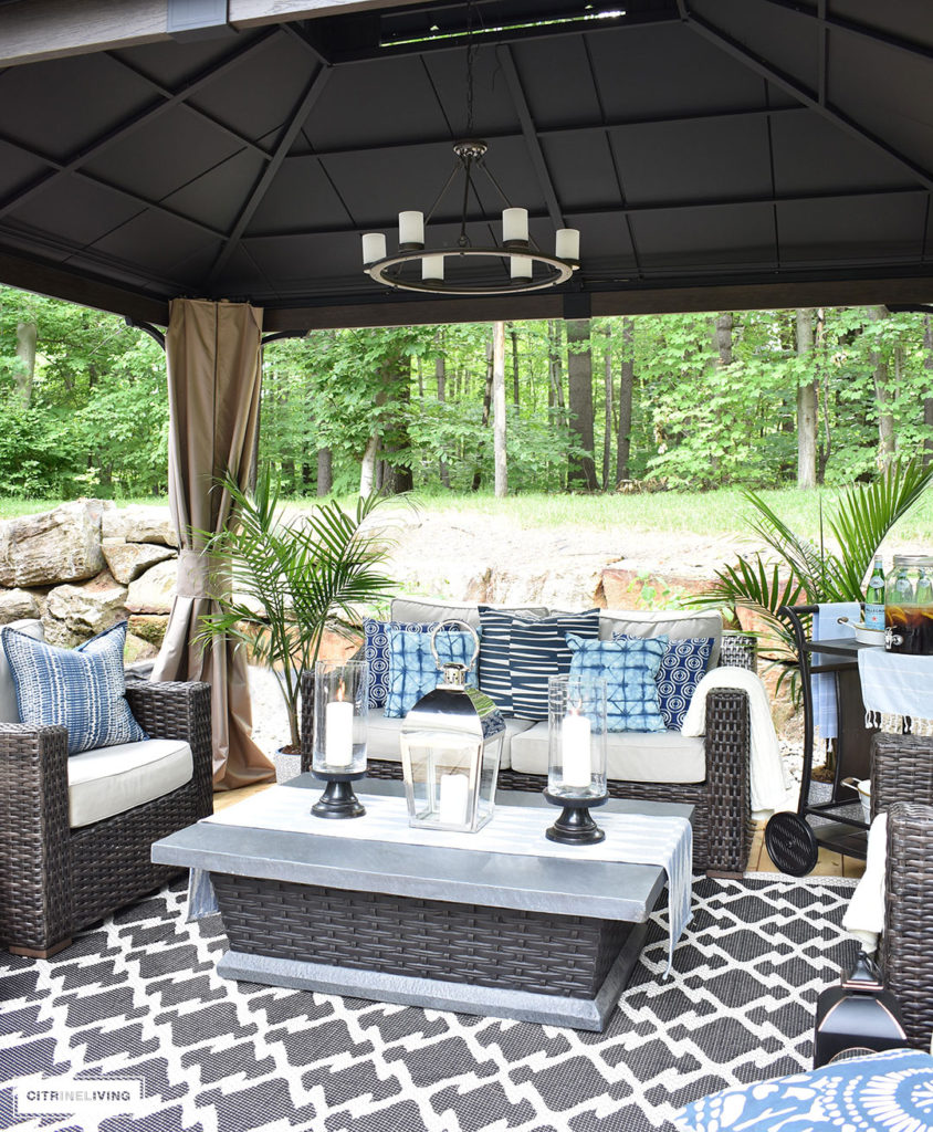 Create the perfect lounging area in your backyard with a beautiful covered gazebo, with added height for an airy, open feel. A gorgeous fire table, solar chandelier, resin wicker furniture, and layered accessories create an elegant and sophisticated look.