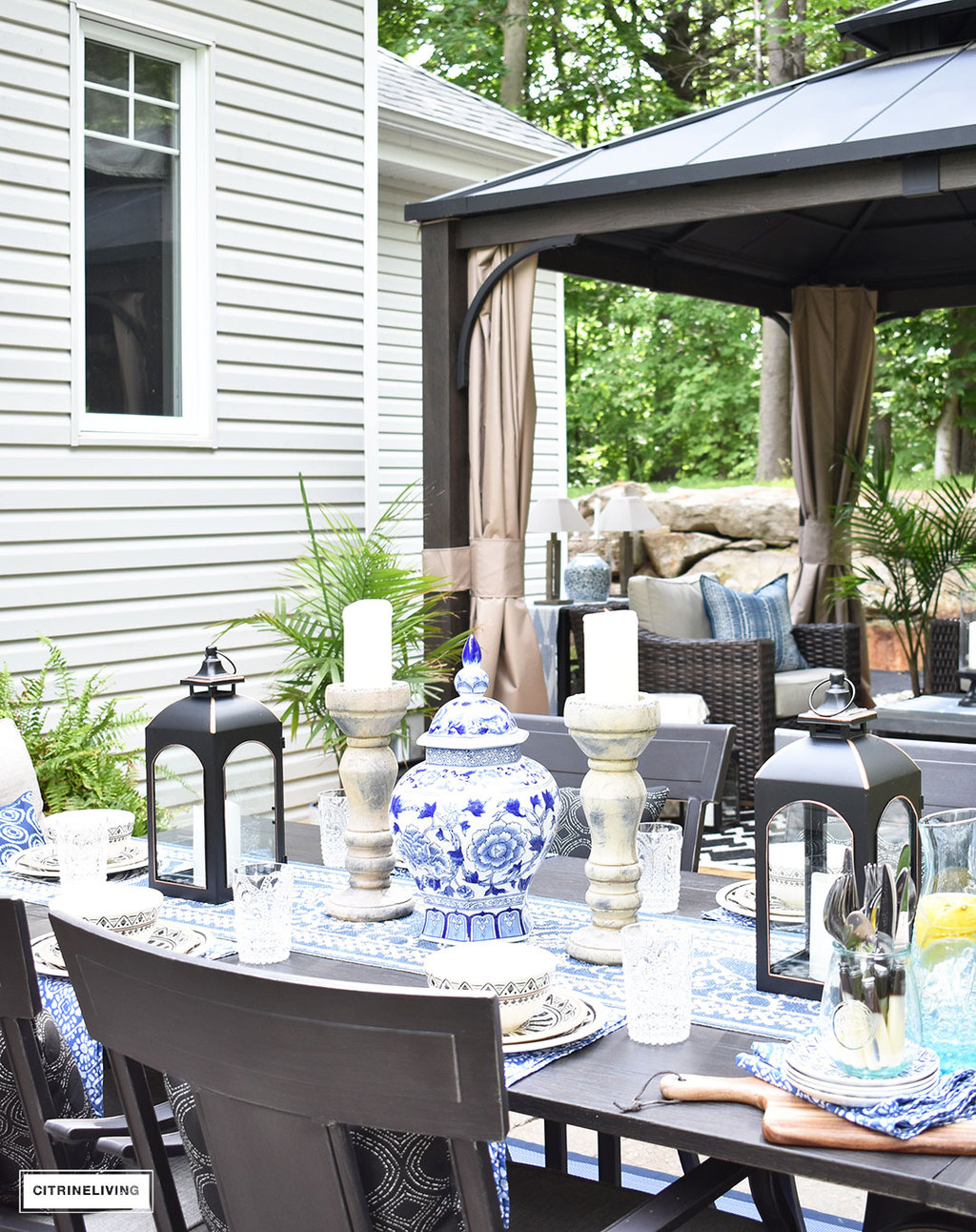 Backyard patio with dining and lounge areas - blue and white striped outdoor rugs and accents bring an indoor look outdoors.