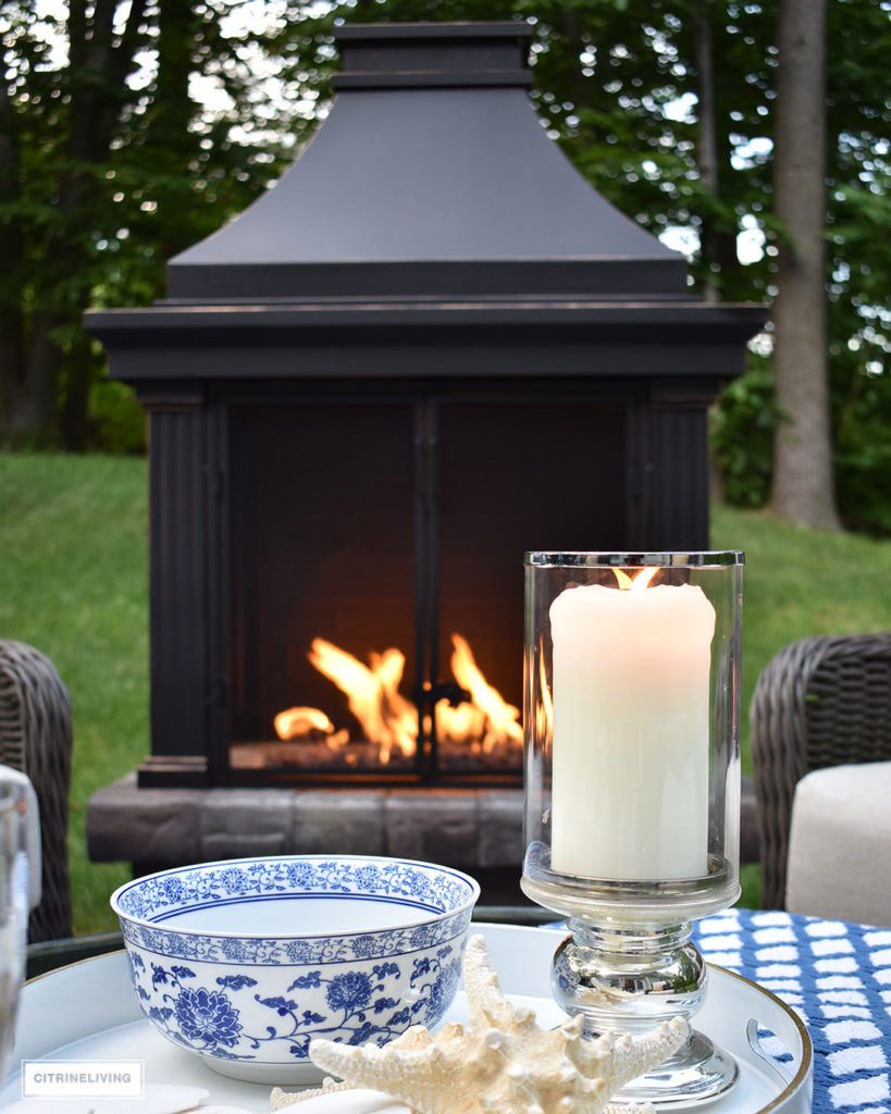 Classic blue and white, hurricane candles and starfish bring a touch of coastal life to this backyard conversation area. Stay warm on chilly nights with a fireplace that everyone can gather around!