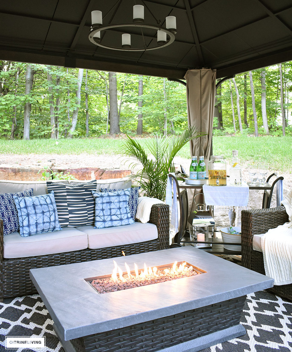 Create the perfect lounging area in your backyard with a beautiful covered gazebo, with added height for an airy, open feel. A gorgeous fire table to keep warm on chilly nights, solar chandelier, resin wicker furniture, and layered accessories create an elegant and sophisticated look.