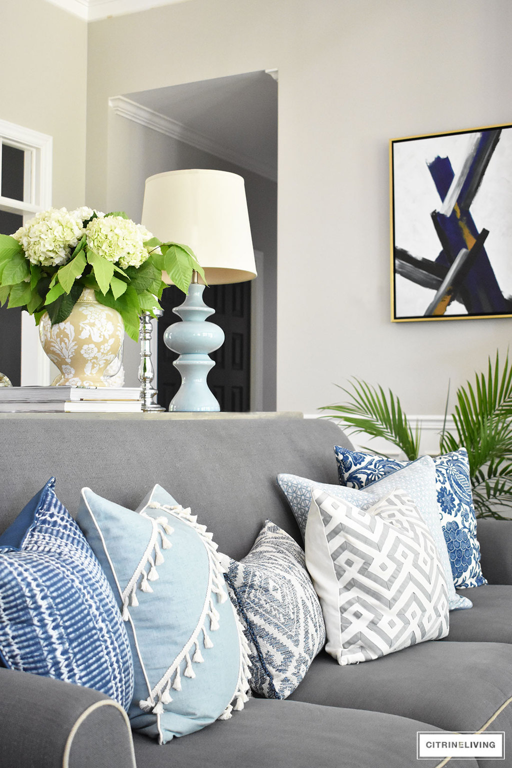 Summer decorated living room with layers of beautiful blue patterned pillows accented with fresh greenery and hydrangeas.