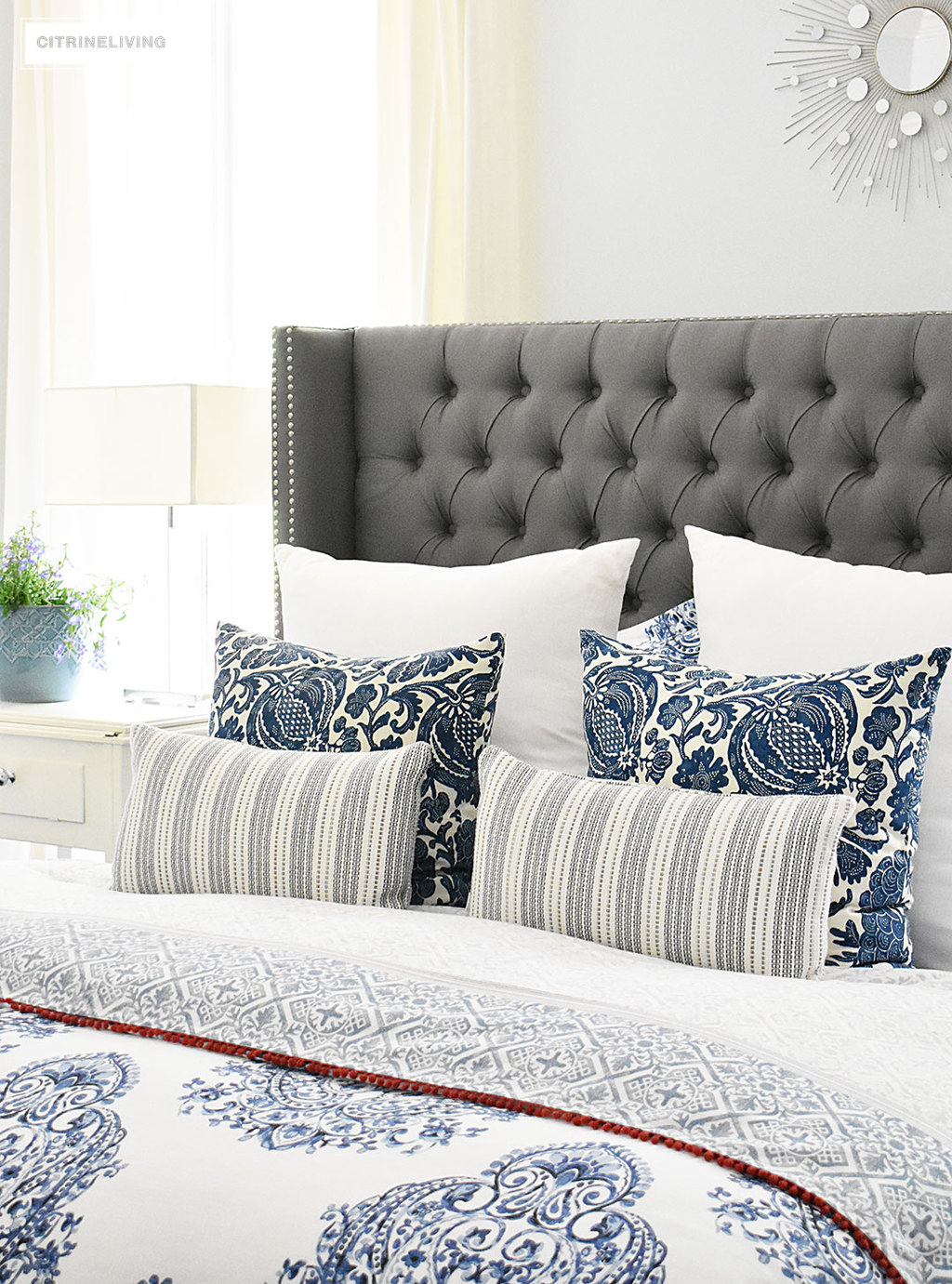 Blue and white Summer decorated bedroom with layers of bold pattern - batik, stripes and paisley - bring a casual, coastal look. Upholstered headboard with nailhead trim is classic and elegant. Light blue walls keep the look crisp and airy.