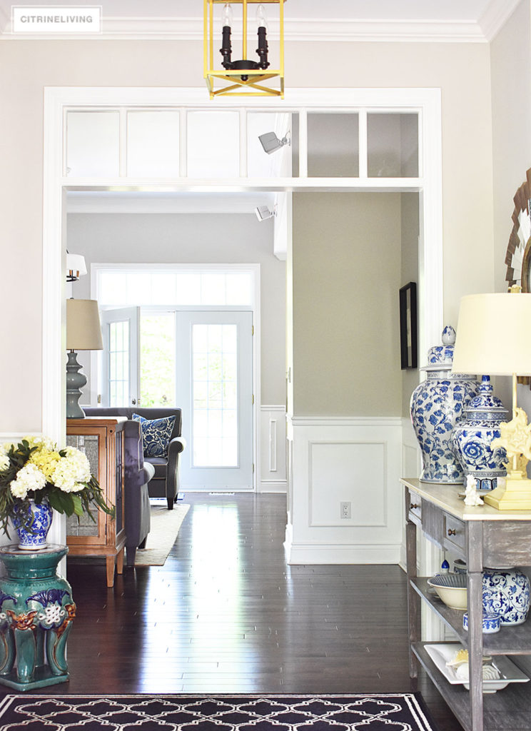 Large entryway with transom details lead to an open concept floor plan. Summer decorating with blue and white accents and fresh greenery keep the look light.