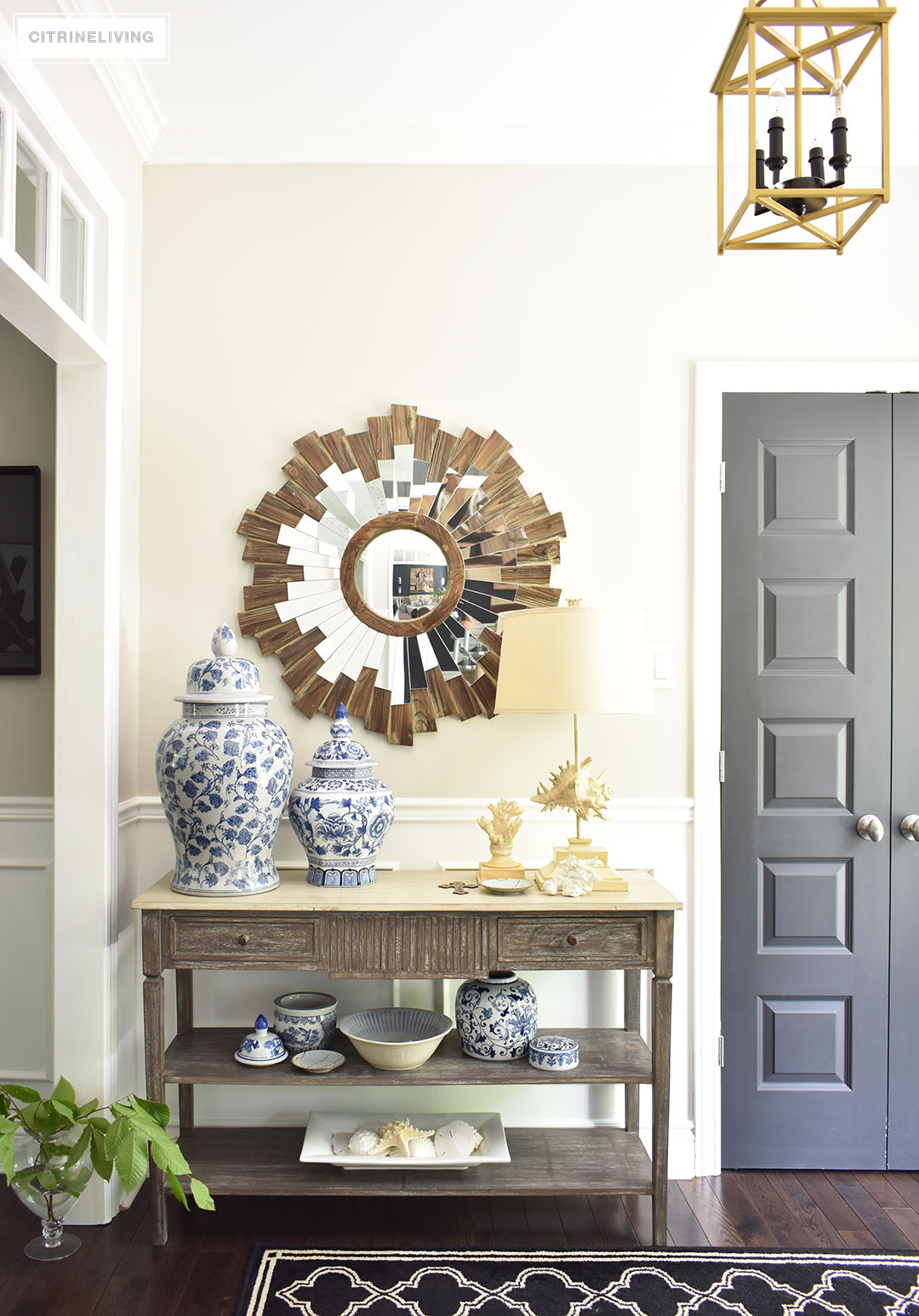 Large entryway with transom details lead to an open concept floor plan. Summer decorating with blue and white accents and fresh greenery keep the look light. Brass lantern style lighting and starburst mirror, a black and white graphic patterned rug help bring a sophisticated look.