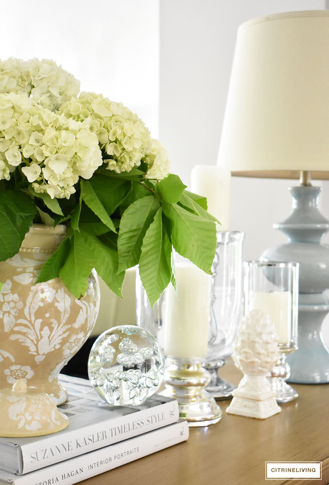 Fresh hydrangeas arranged in a classic ginger jar paired with glass hurricanes is the perfect touch of Summer decor in any room.
