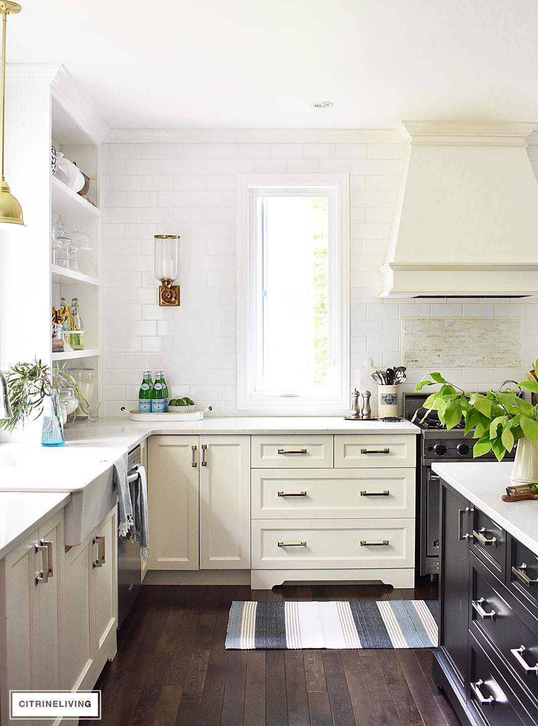 White kitchen with black island decorated for Summer with blue and white ginger jars and dishes accented a blue and white striped rug and turkish towels and fresh cute greenery.