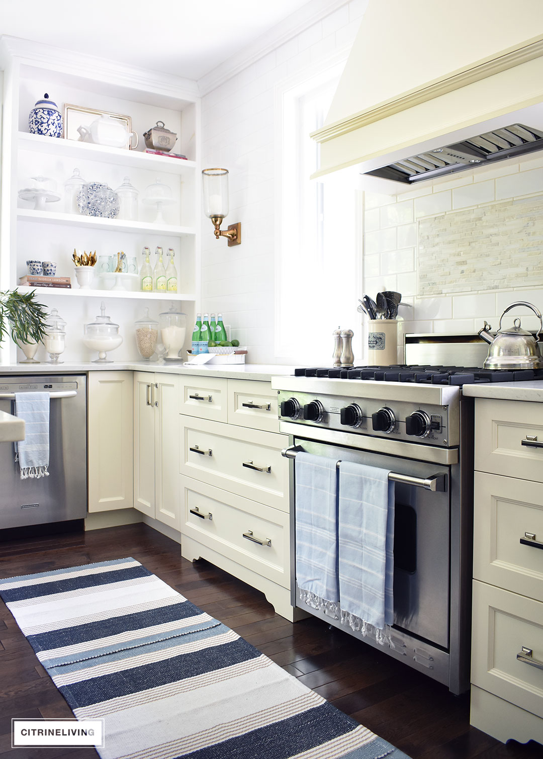 White kitchen decorated for Summer with blue and white ginger jars and dishes accented with a coastal blue and white striped rug and turkish towels. Open shelving to display dishes and serving pieces makes a strong statement.